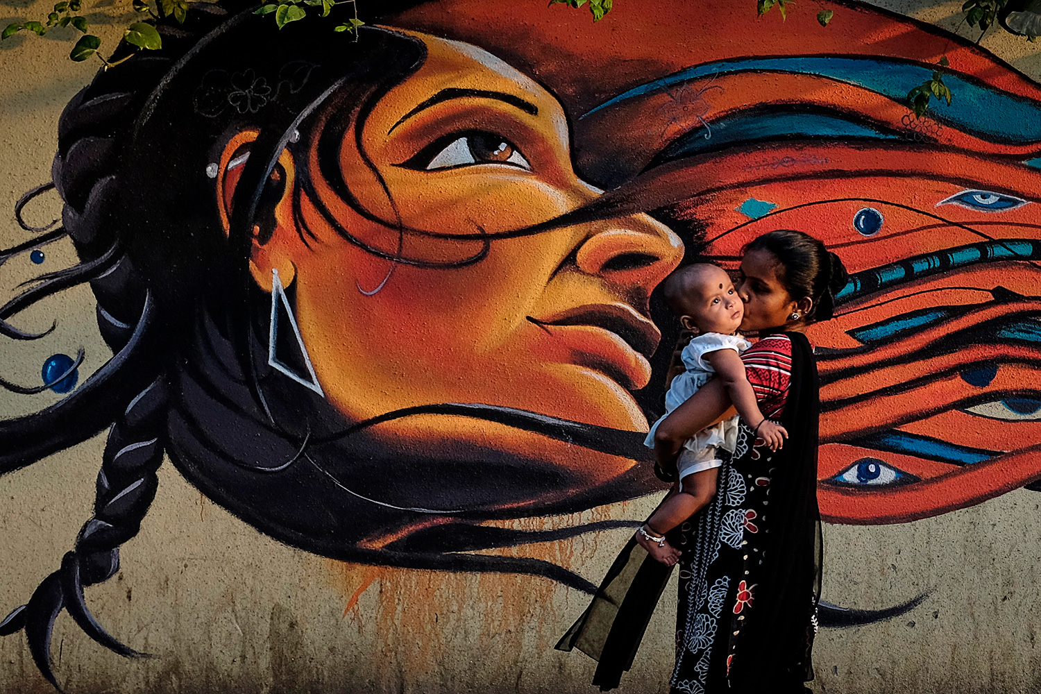The image is striking with a large, artistic image behind a woman who is walking and holding a child.