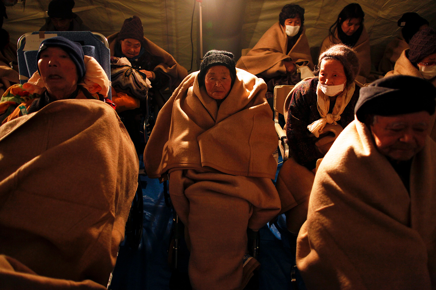 Photo shows a half dozen people all wrapping themselves in generously sized fluffy brown blankets.