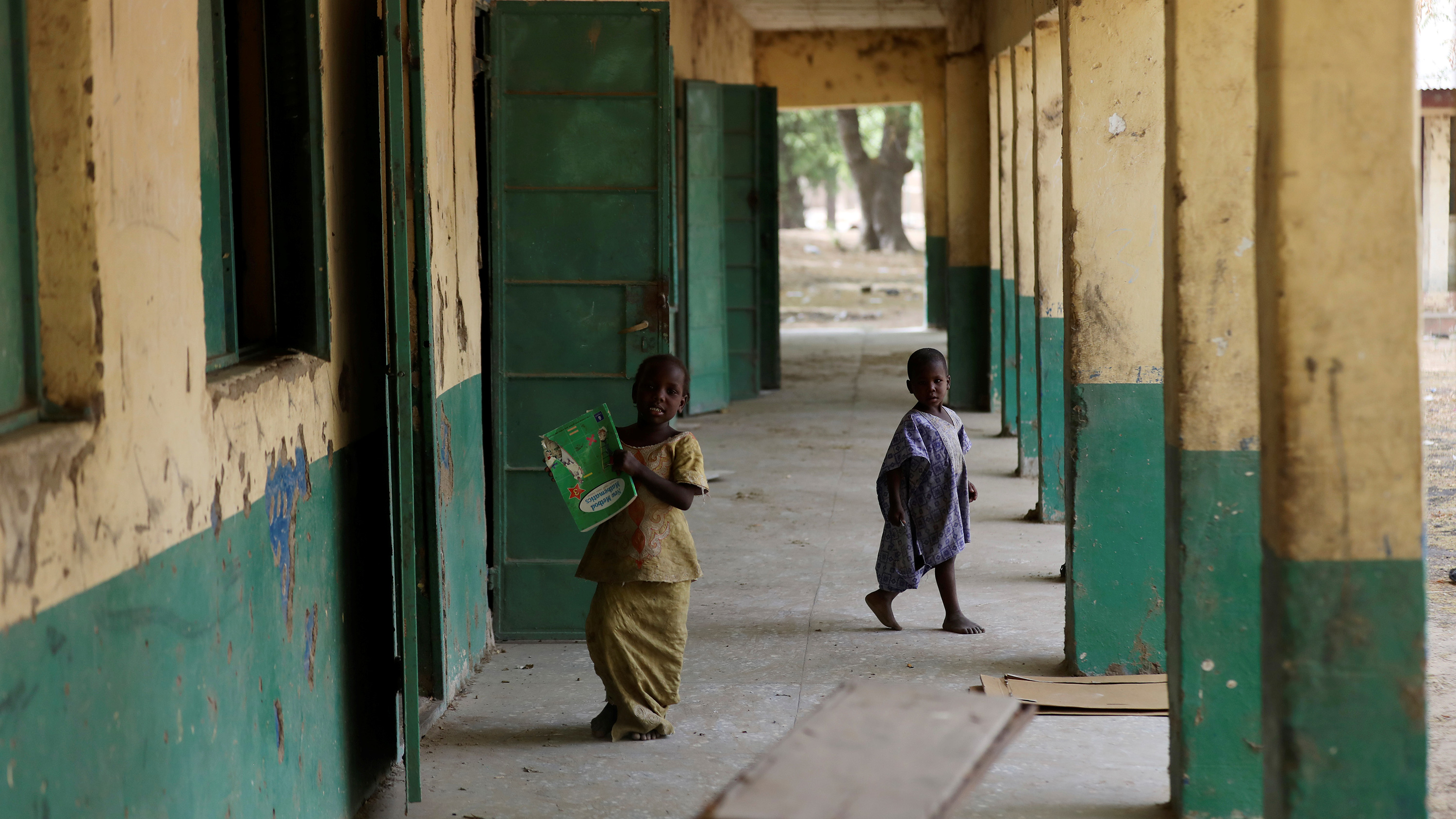 Picture shows two children walking along an outdoor corridor at a school with large cinder block columns painted green.