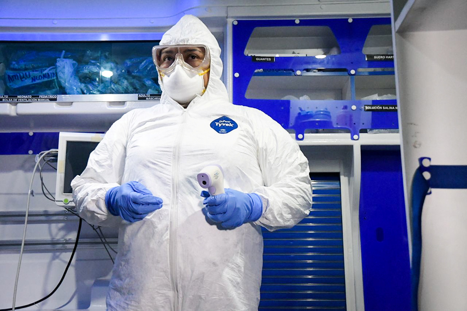 Image shows a worker fully garbed in protective gear head to toe holding a thermometer. Everything in the picture strikingly white or blue.