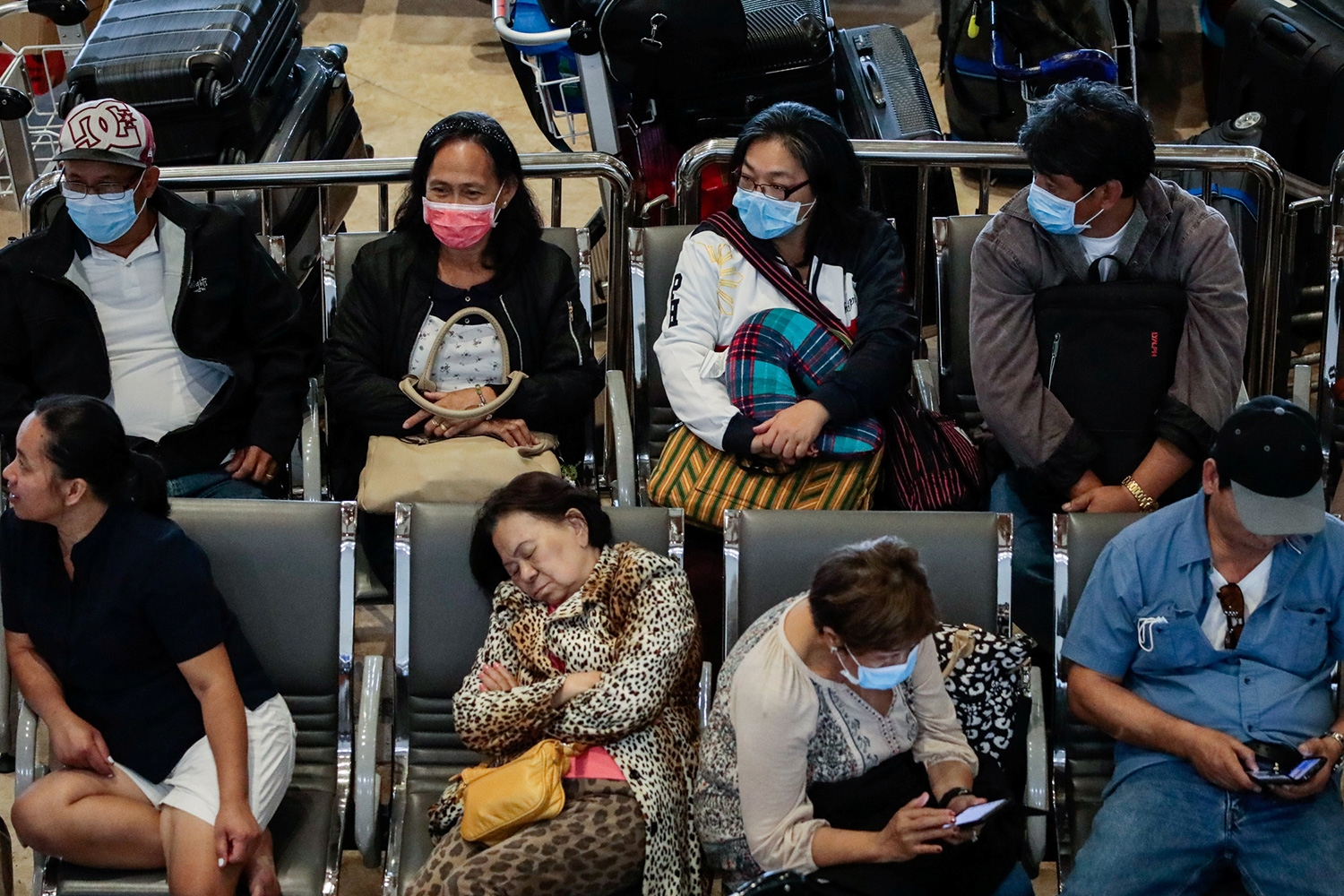 The photo shows people sacked out in airport chairs, some asleep, some on their cell phones, almost all wearing masks.