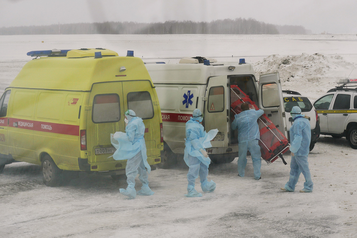 The photo shows several workers in blue protective suits standing outside their ambulances in what appears to be freezing weather.