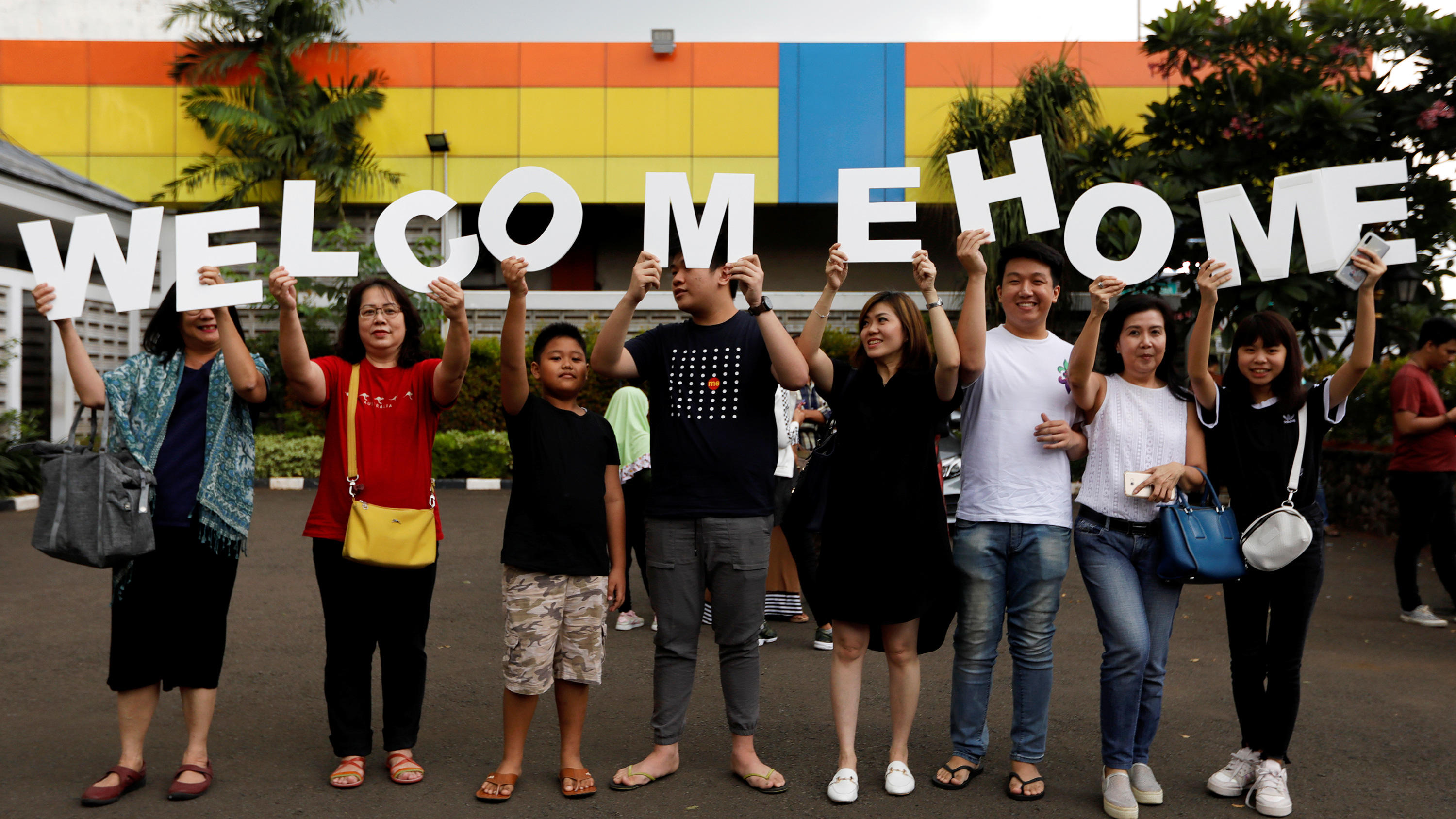 This is a fun photo of a large extended family standing in a parking lot holding a sign that reade welcome home.