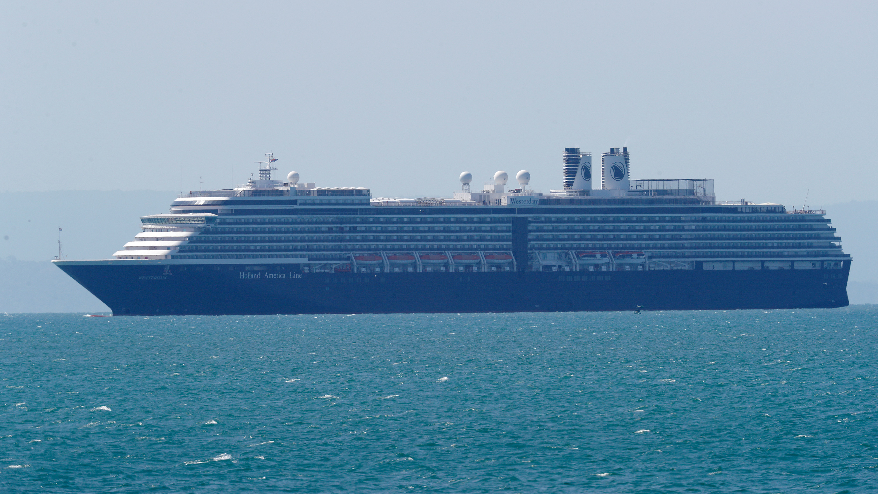 The photo shows a massive luxury cruise ship off in the distance, in a photo presumably taken from shore.