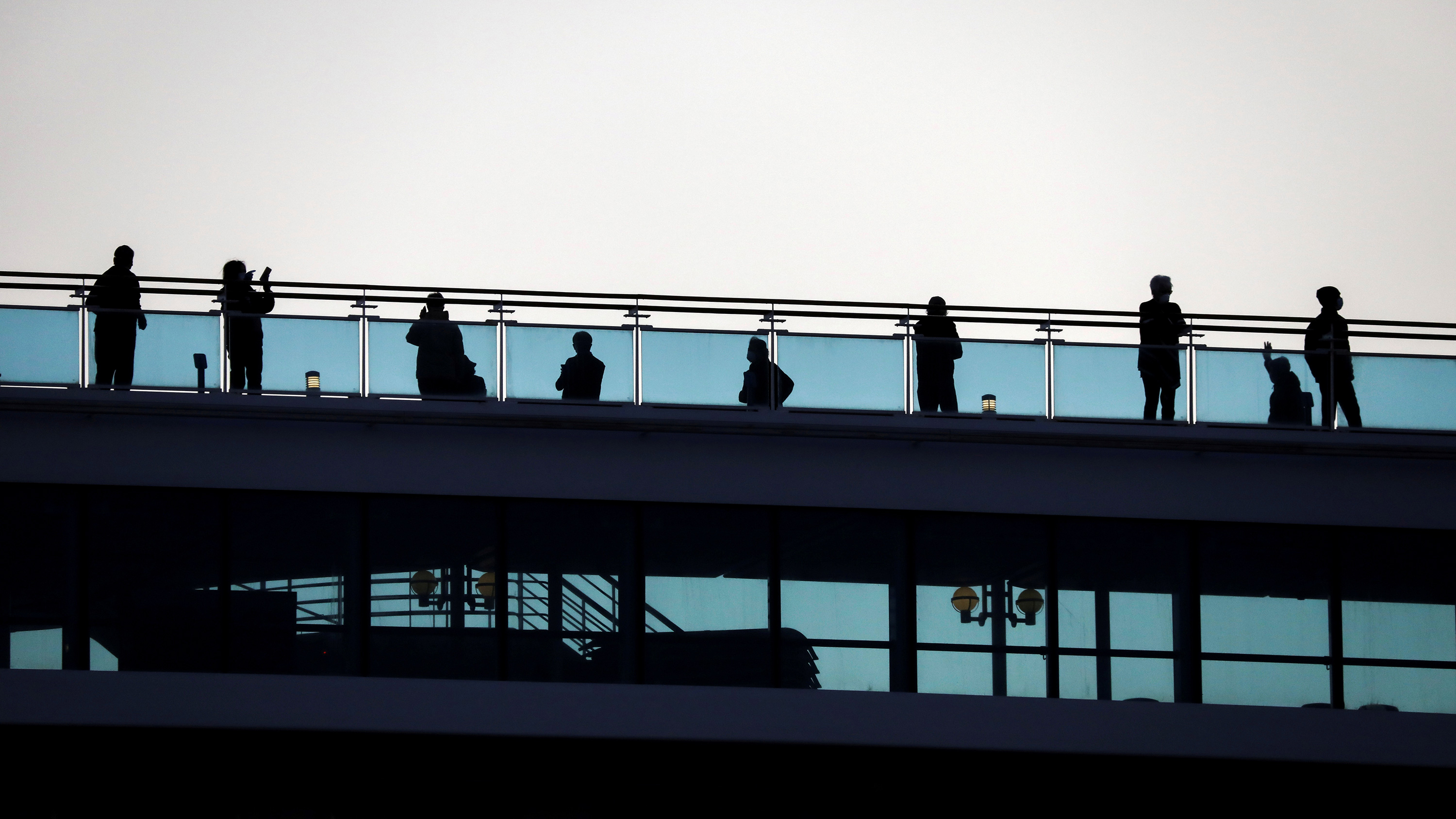 The image shows a couple rows of passengers on two decks, one below the other. They are standing against a bright background and appear as silhouettes.
