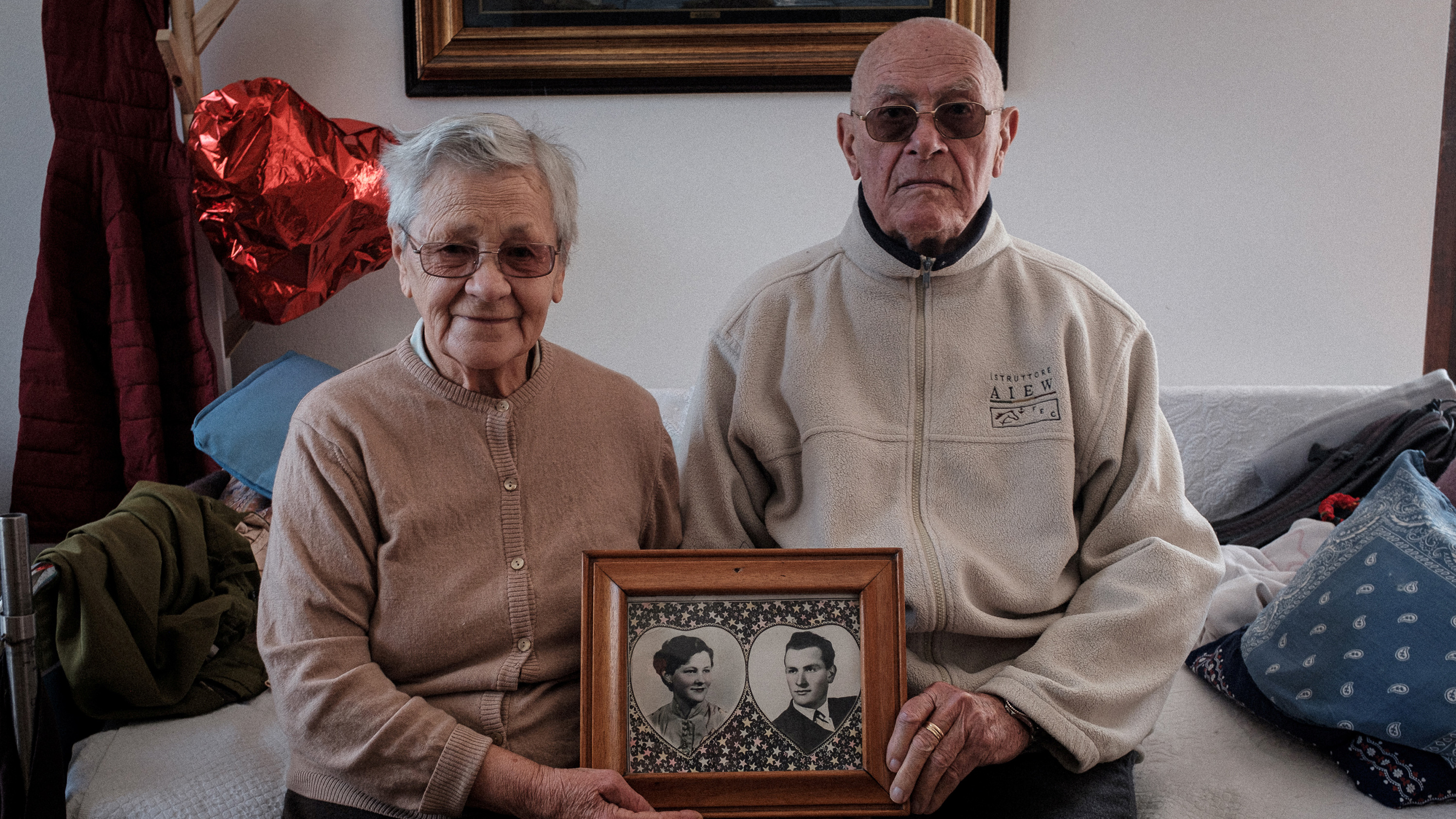 Picture shows the elderly couple sitting together holding a picture of the two of them taken many years before. They are a cute couple.