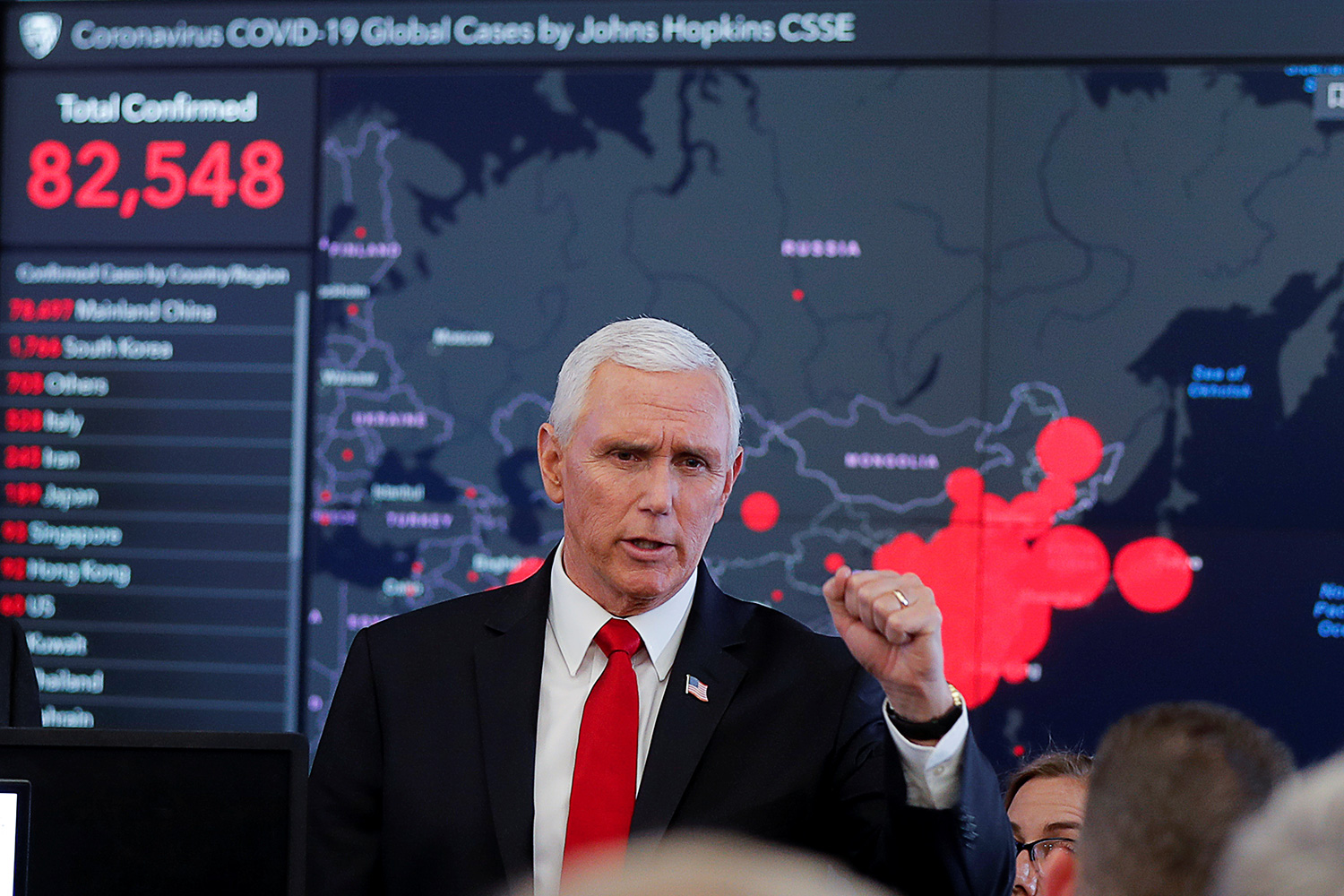 The picture shows Pence standing in front of a huge screen with situation data on it.