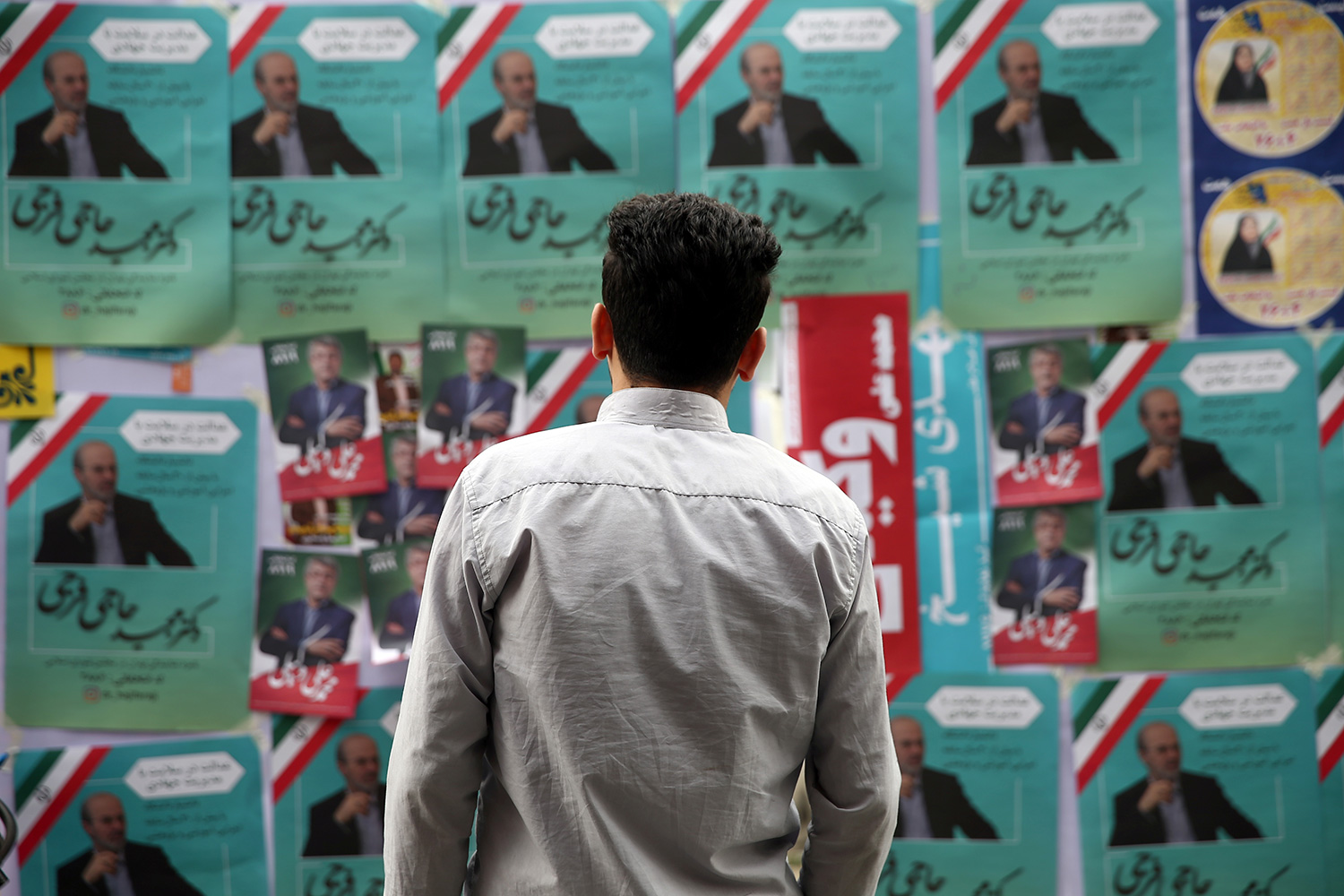 A man looks at parliamentary election campaign posters in Tehran, Iran on February 19, 2020. The photo shows the man standing in front of a board that is placarded with multiple political campaign posters, many of them identical and pasted over and over. The predominant colors are green, white, and red—like the Iranian flag. WANA/Nazanin Tabatabaee via REUTERS.