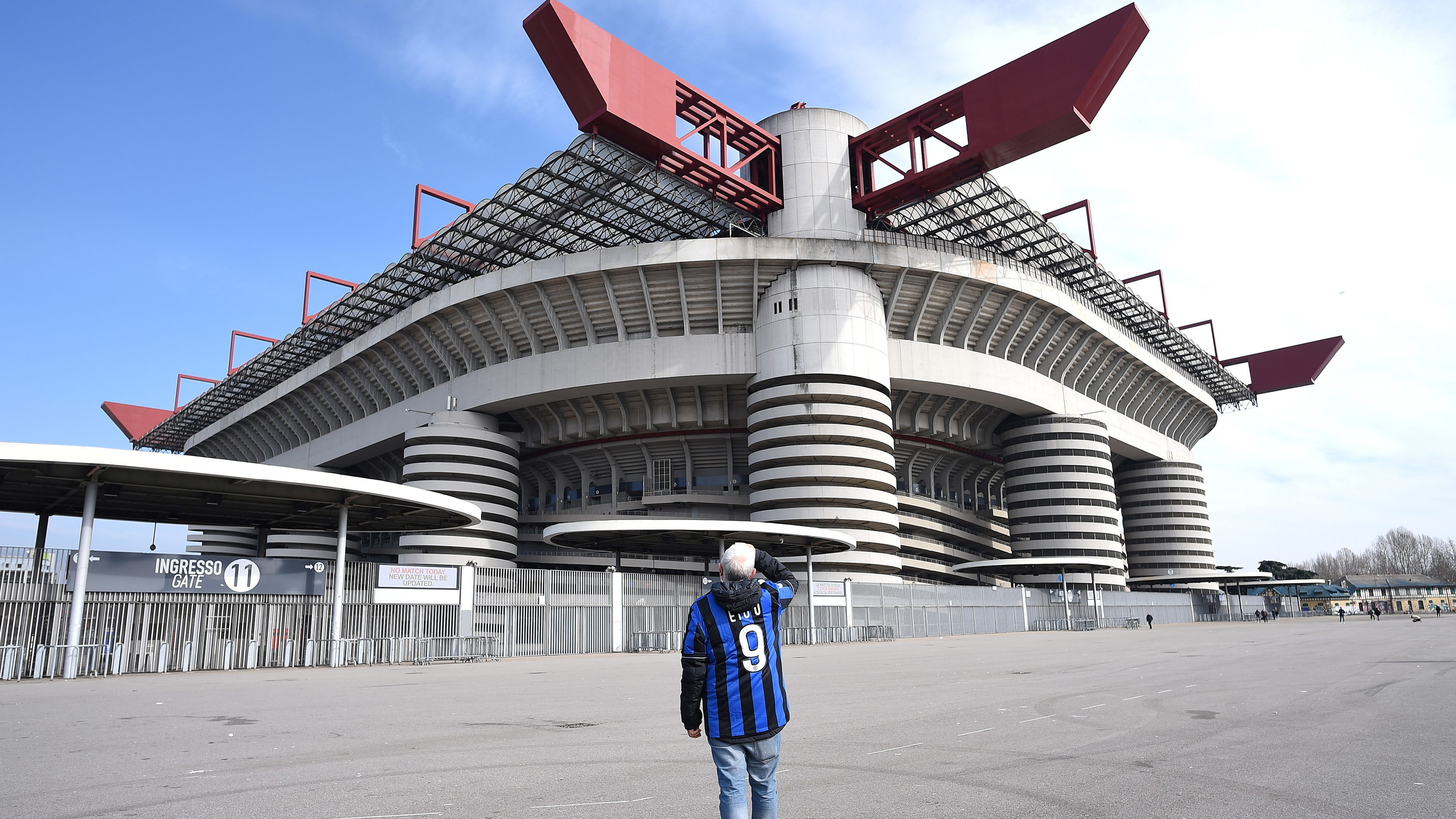 The picture shows a man wearing a fan jersey in an empty lot in front of a massive stadium.