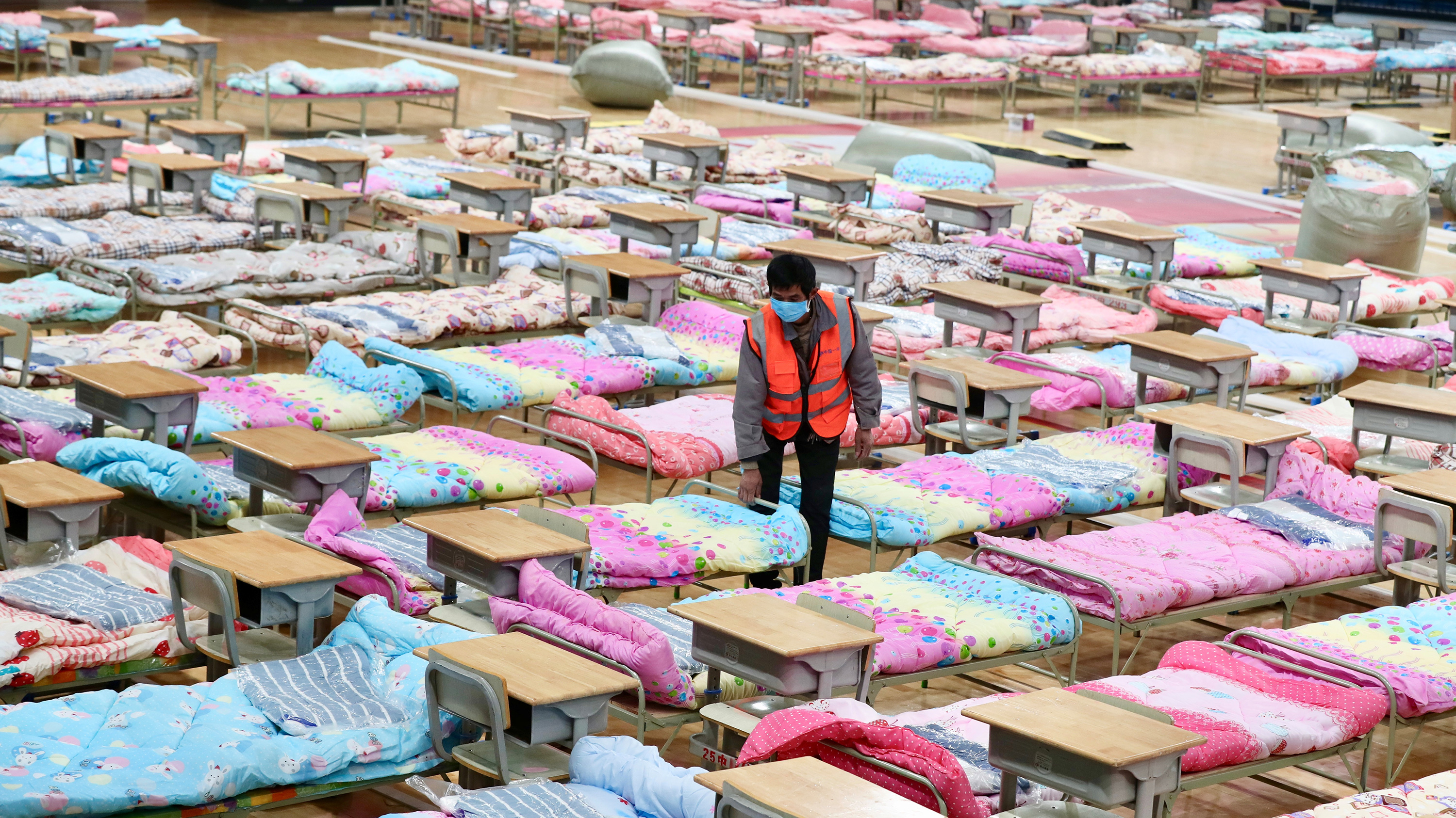 The photo shows a worker adjusting the covers on a bed in a large space filled with hundreds of cot-sized beds covered with white and pink and blue bedding.