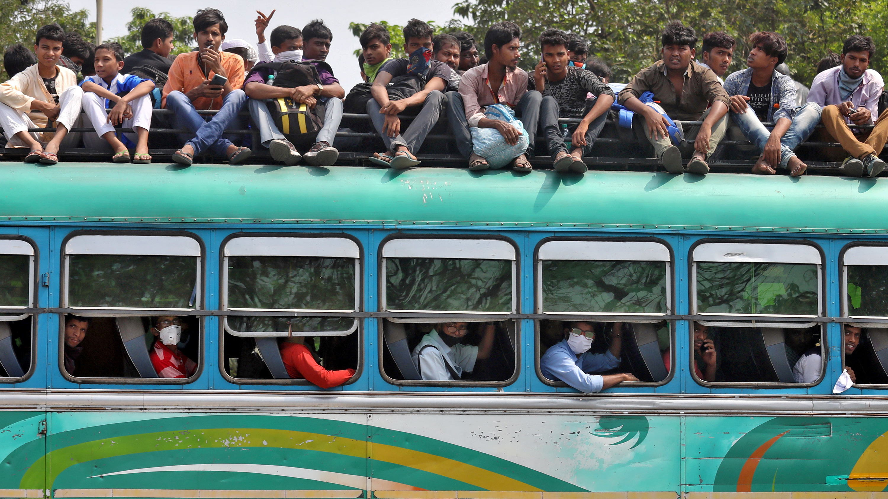 The image shows a green bus, its seats full, with many people sitting on top of the vehicle.