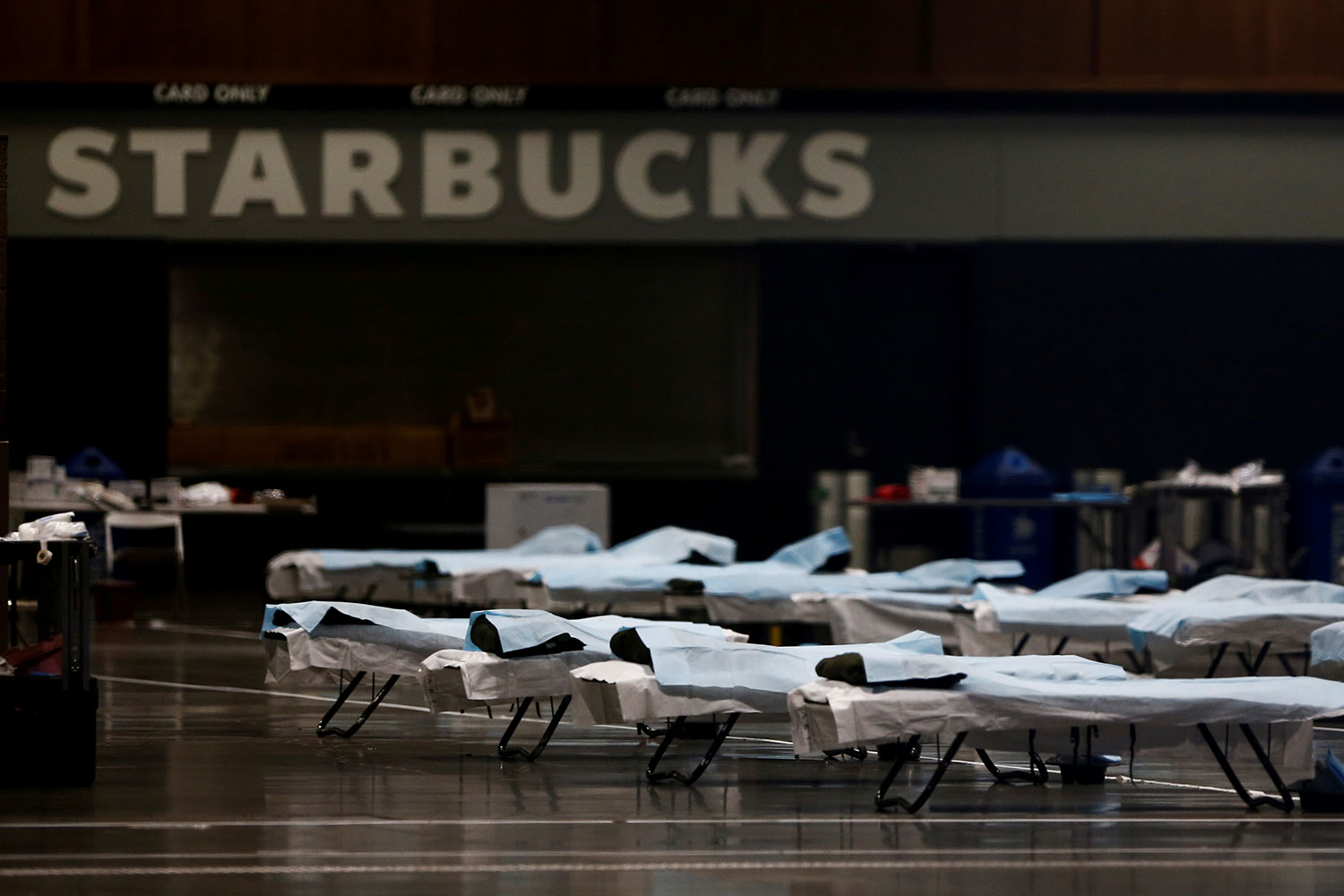 The photo shows a large number of beds lined up in a large open space with a Starbucks sign in the background.