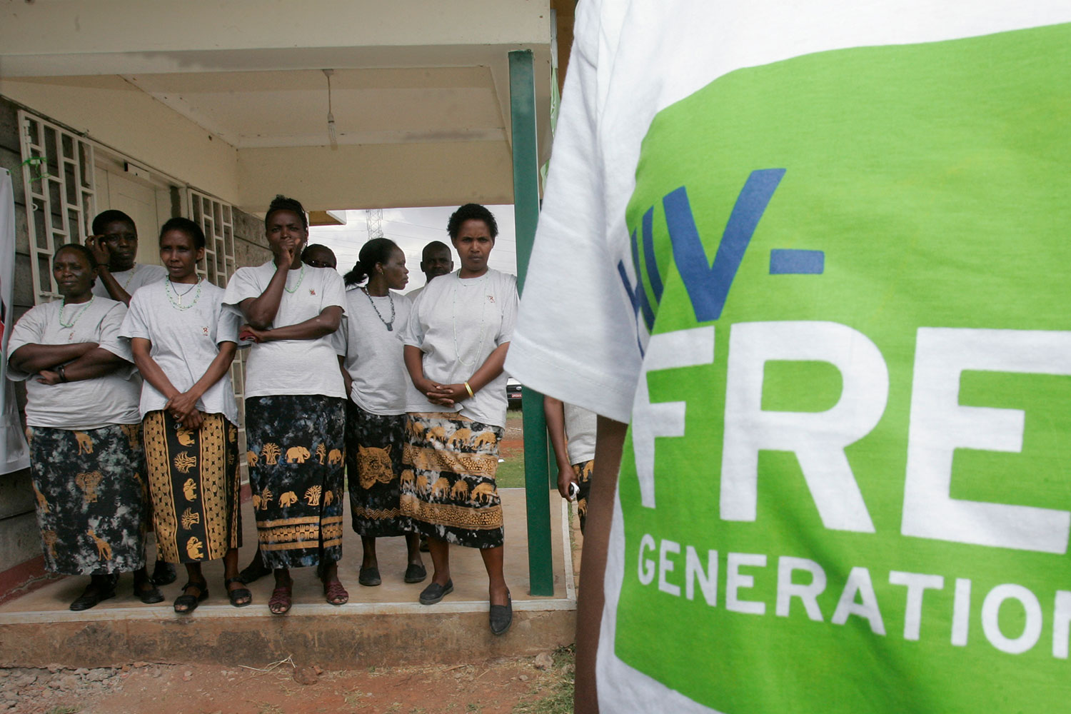 "The photo shows several people about 20 feet from the camera standing and listening while a figure stands in the foreground. The camera is too close to see their face, but they are wearing a Tee Shirt that says, ""HIV-free Generation."""