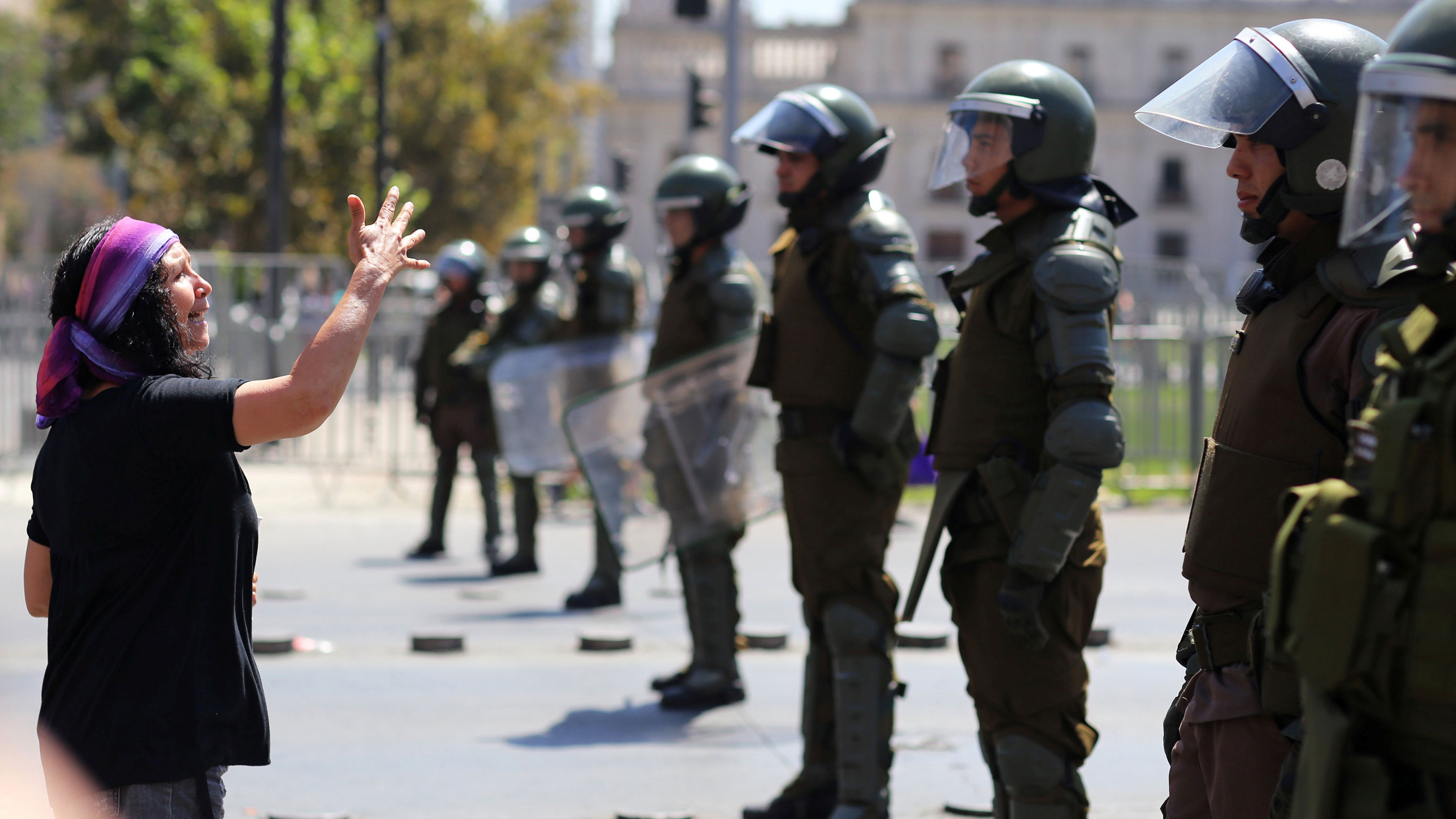 This is a striking photo where a woman wearing a colorful bandana is shouting at a line of police wearing riot gear and gesturing with her hand.