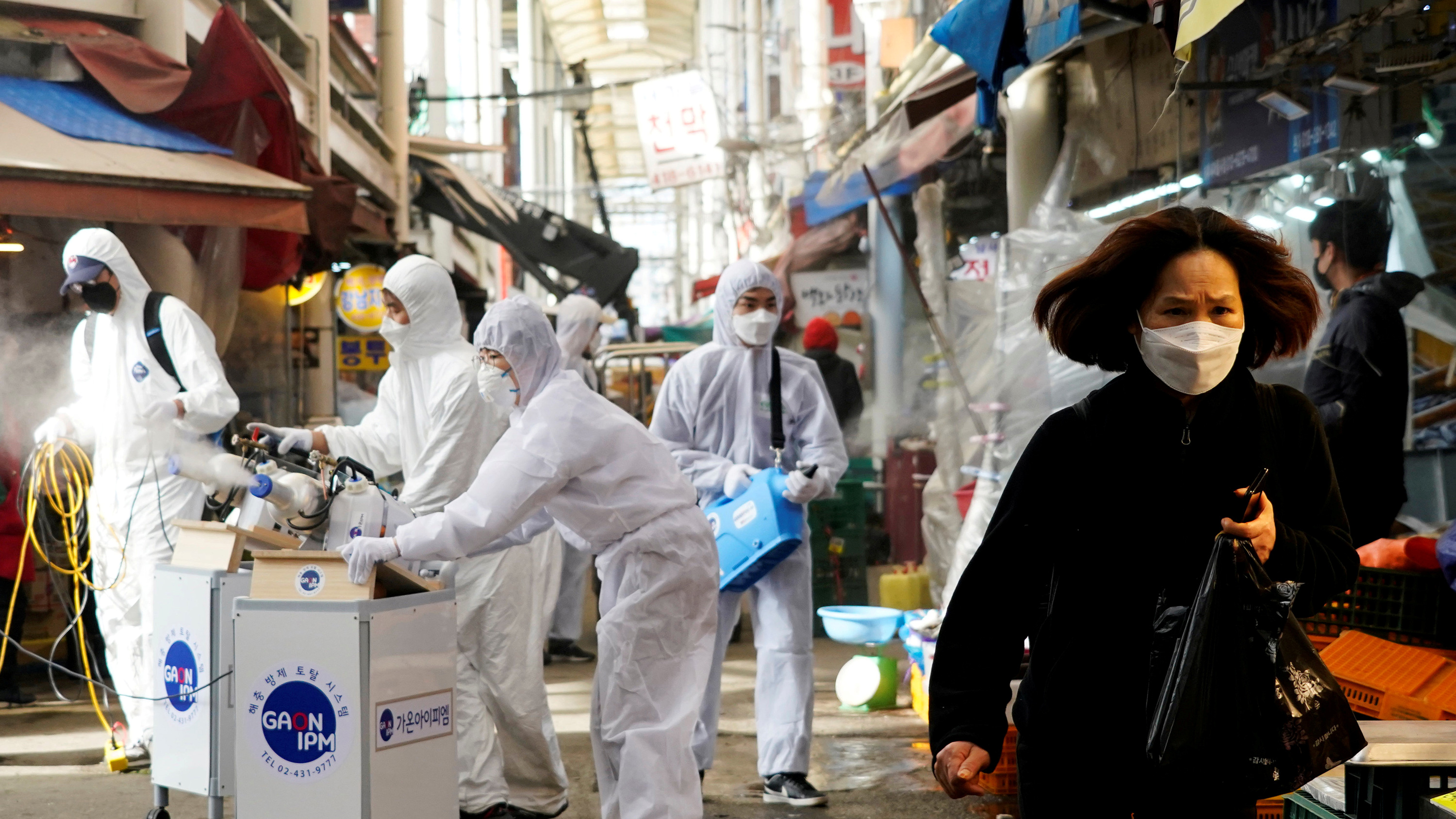 This is a striking image with a woman walking by a crew covered in protective gear spraying a substance on the streets of what looks like a normally busy market, now almost abandoned.