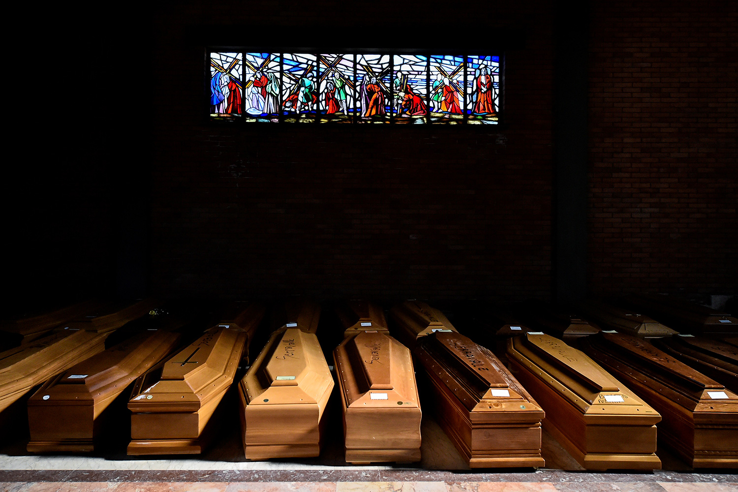 The image shows a huge number of plain coffins in a dimly lit corner of a church beneath a stained glass.