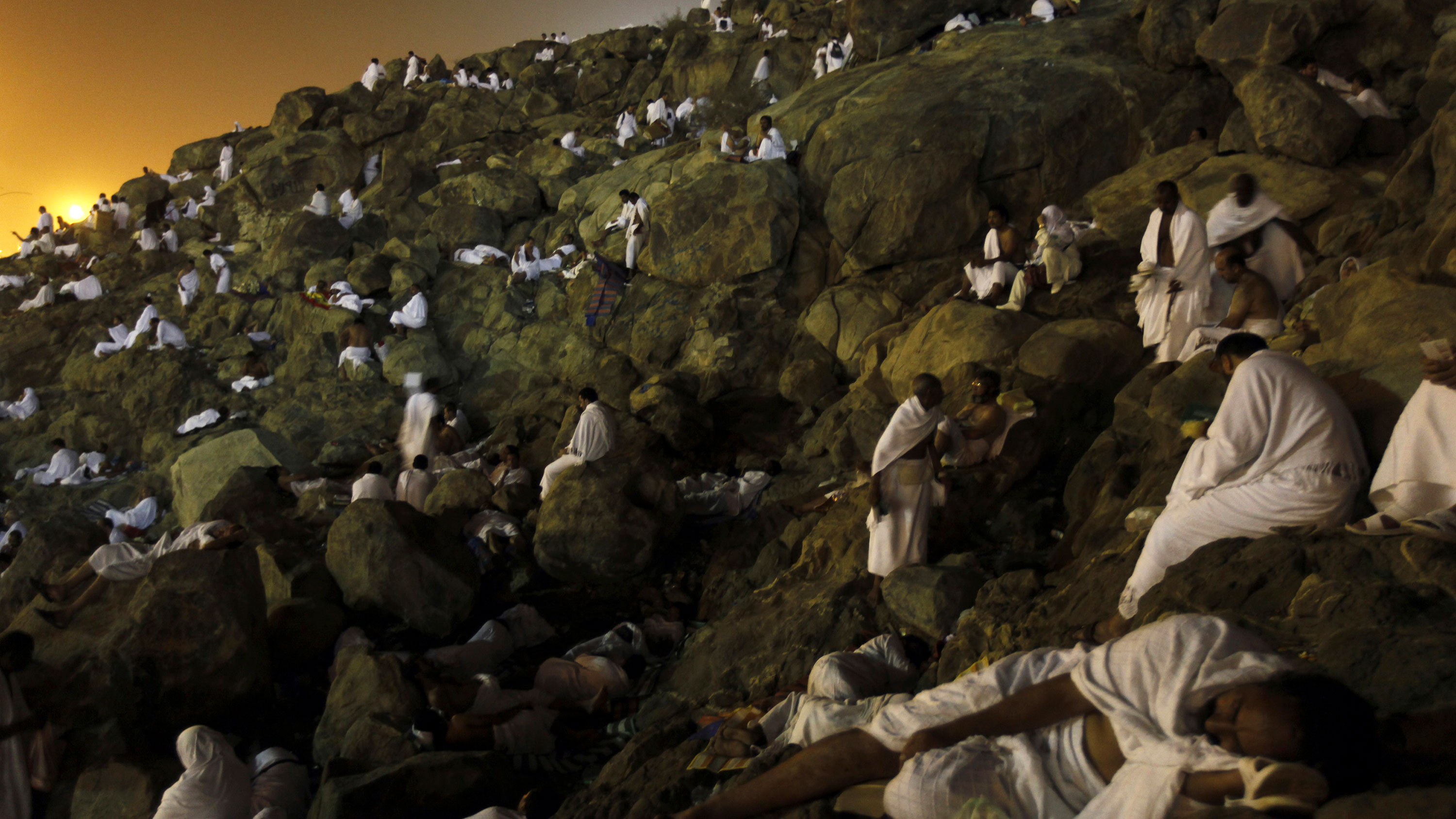 The photo is stunning. Dawn is breaking over the mountain, and hundreds of pilgrims wearing simple white robes are resting on the rocks in twos and threes.