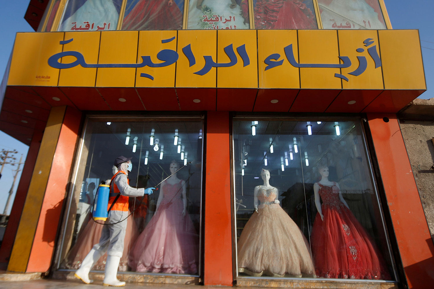 A worker in protective suit sprays disinfectants in front of a dress shop at popular market following the outbreak of the coronavirus in Basra, Iraq on March 10, 2020. This is an interesting photo showing a colorful dress shop with a worker walking by outside in protective gear spraying disinfectant. REUTERS/Essam al-Sudani