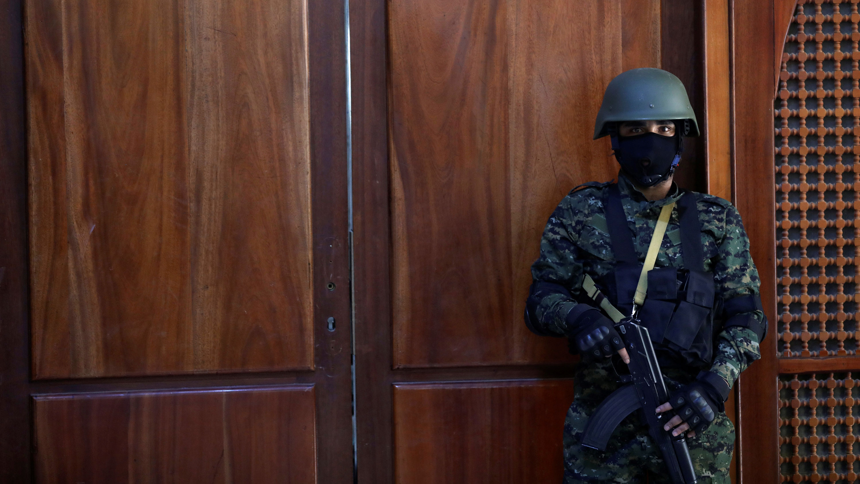 The picture shows a guard with a machine gun standing in front of a wooden door. His mask is black, the door is red.