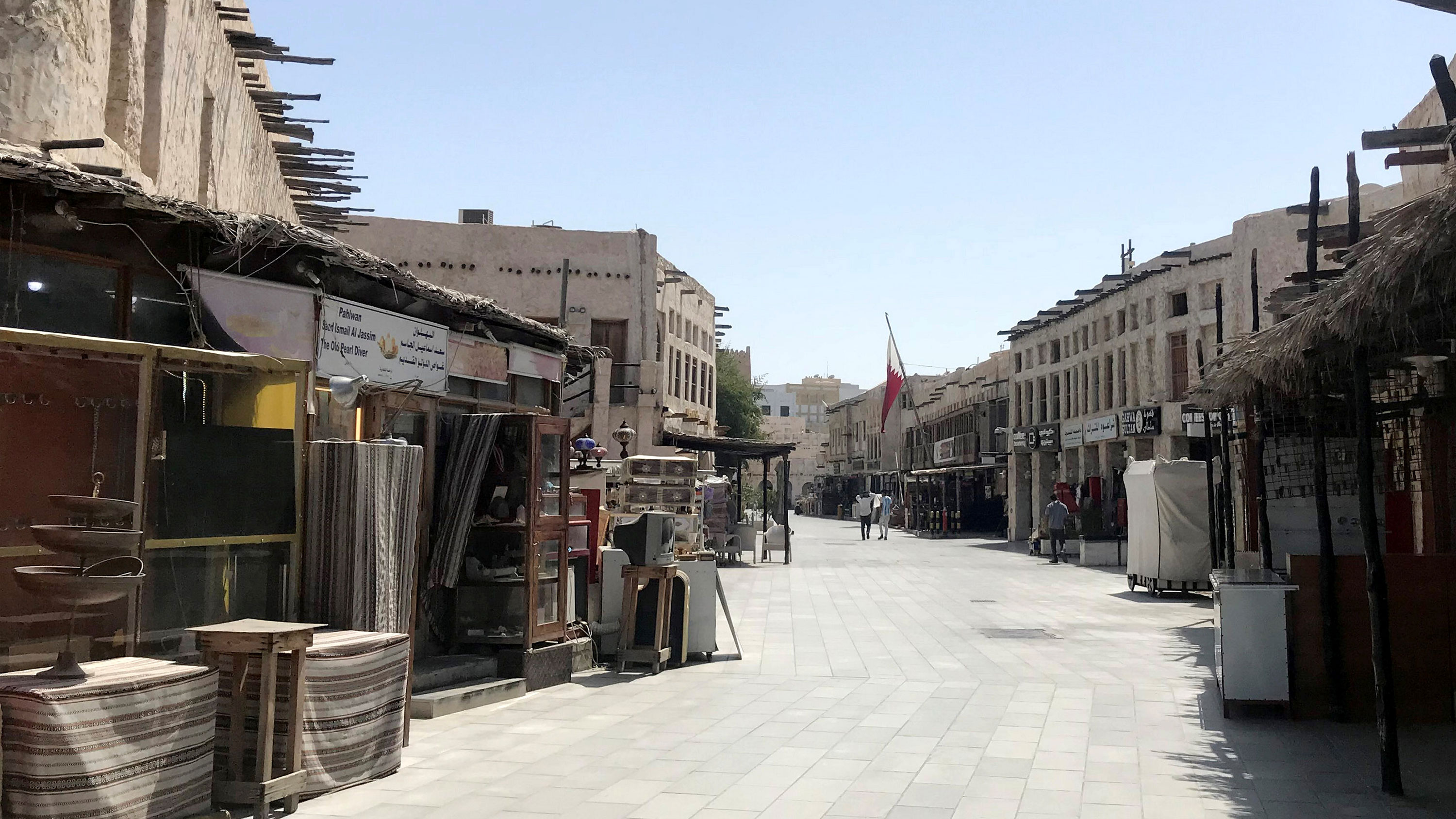 The image shows the empty, mostly abandoned stalls of a Middle Eastern marketplace