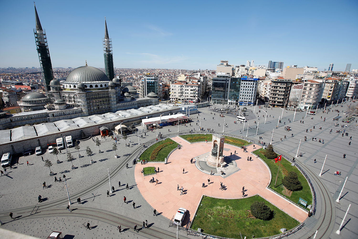 The photo is an aerial shot of the iconic square on a beautiful day with very few people walking around.