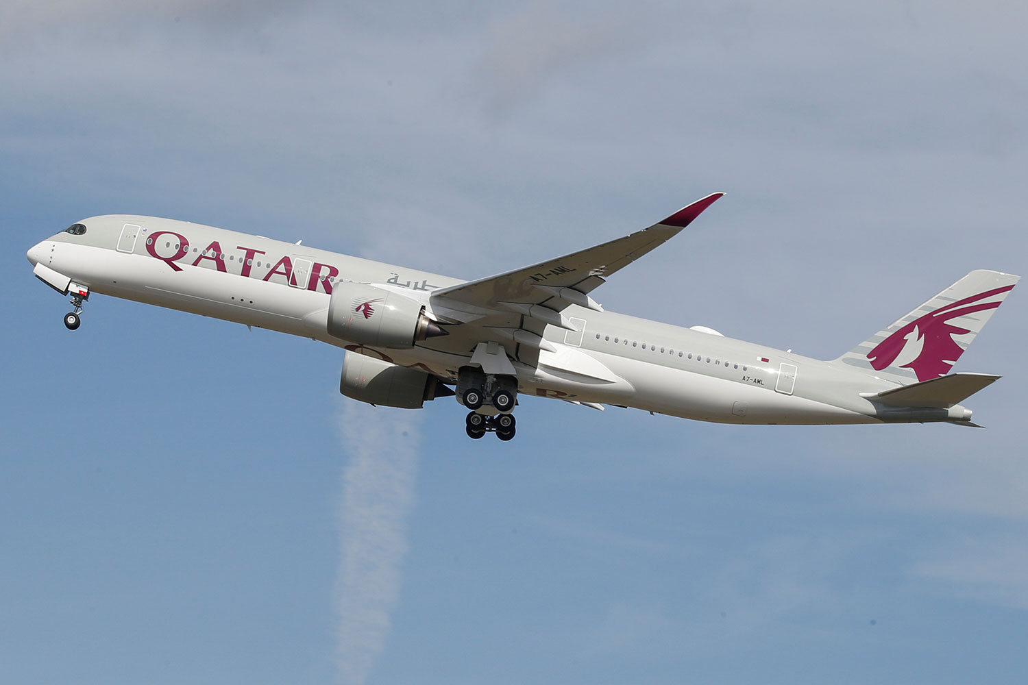 The photo shows a Qatar Airways jetliner in takeoff against a bright blue sky.