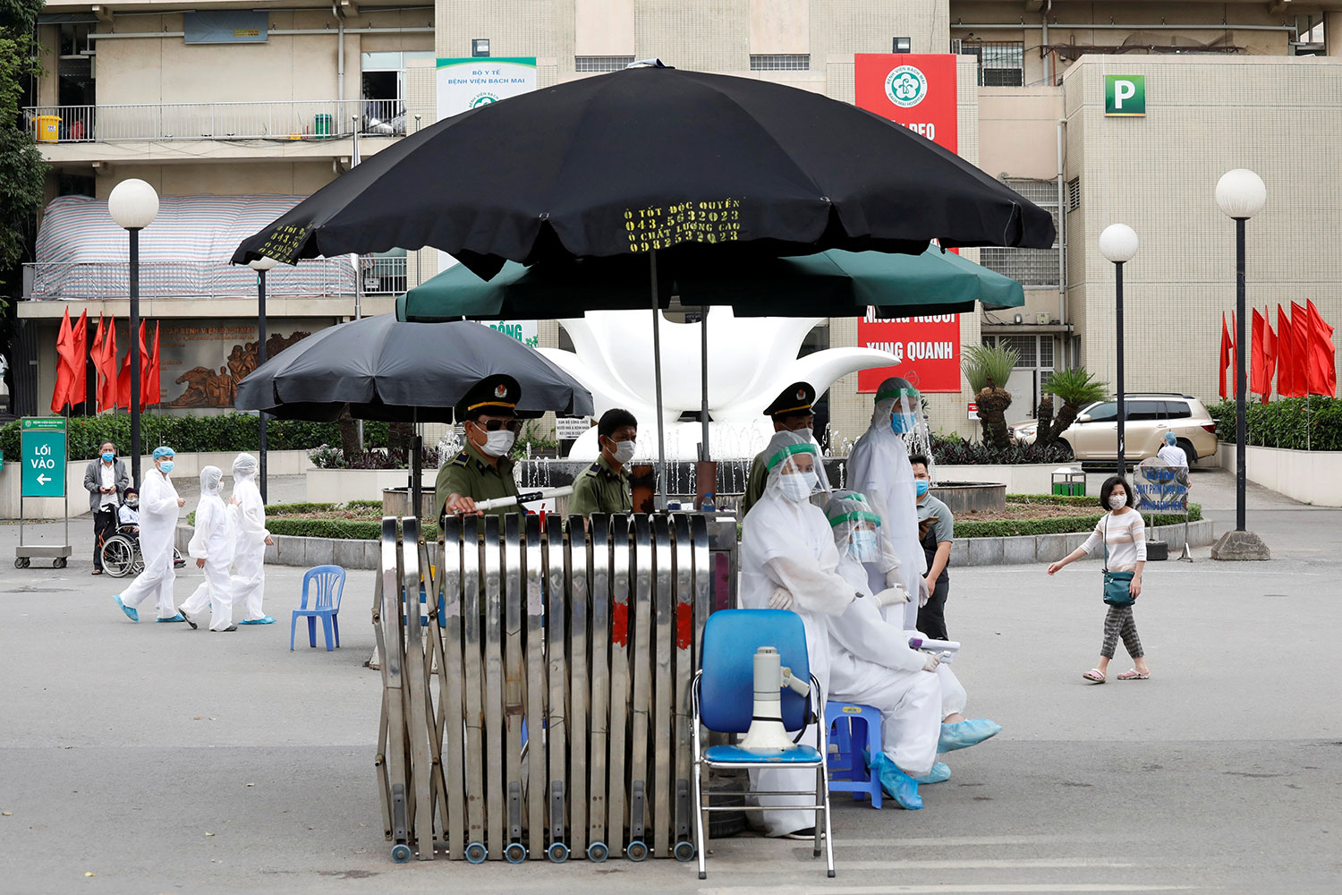 Photo shows the hospital from the outside with a simple triage set up with a black umbrella.