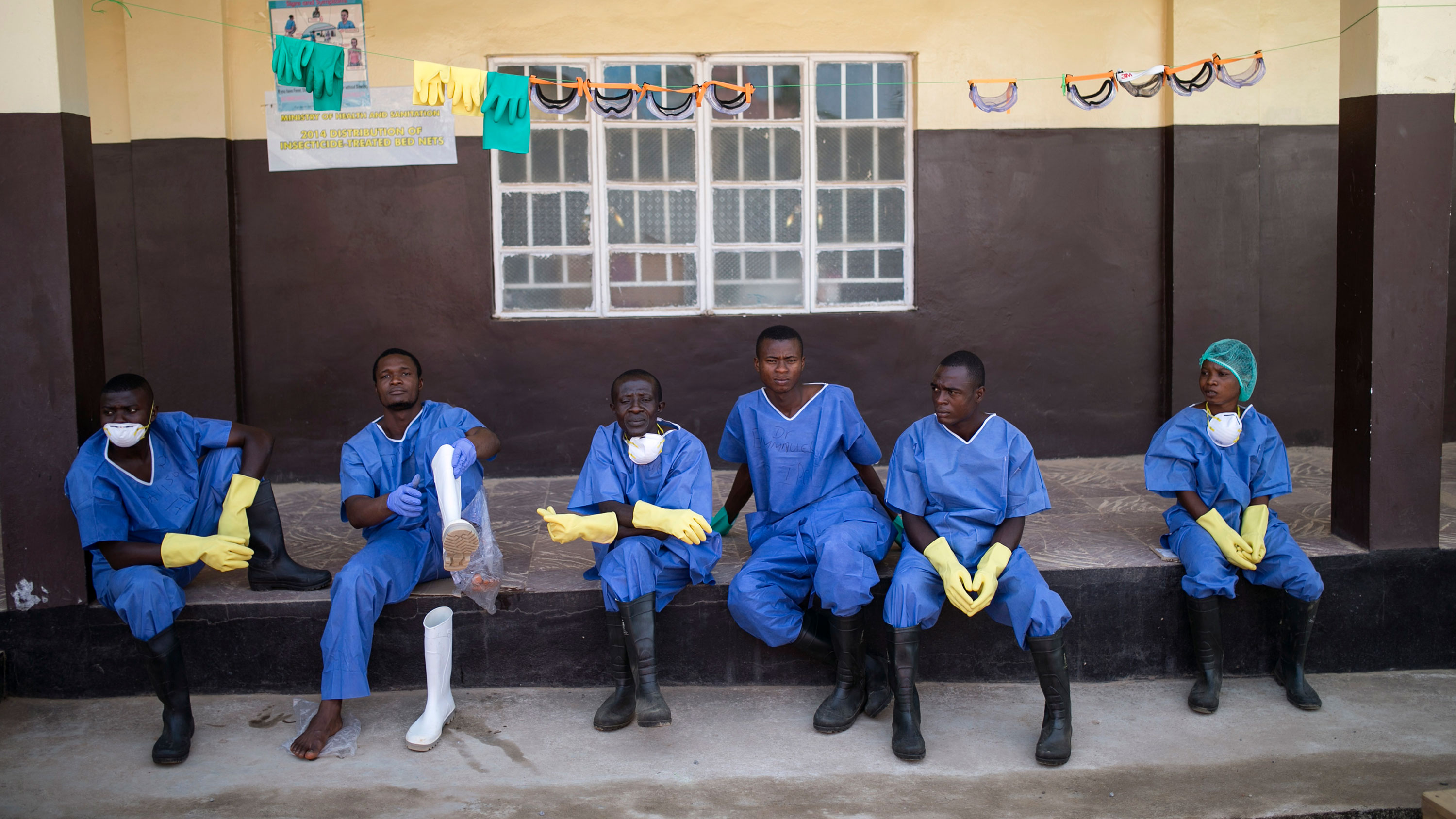 The photo shows six workers on a bench. They are wearing blue scrubs, black boots, and yellow gloves.