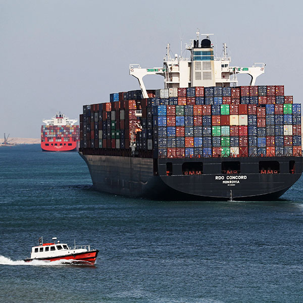 Container ship RDO Concord sails through the Suez Canal on November 17, 2019. The picture places the viewer in the wake of a massive freighter stacked high with metal shipping containers as a smaller patrol-type boat passes in the foreground. REUTERS/Mohamed Abd El Ghany