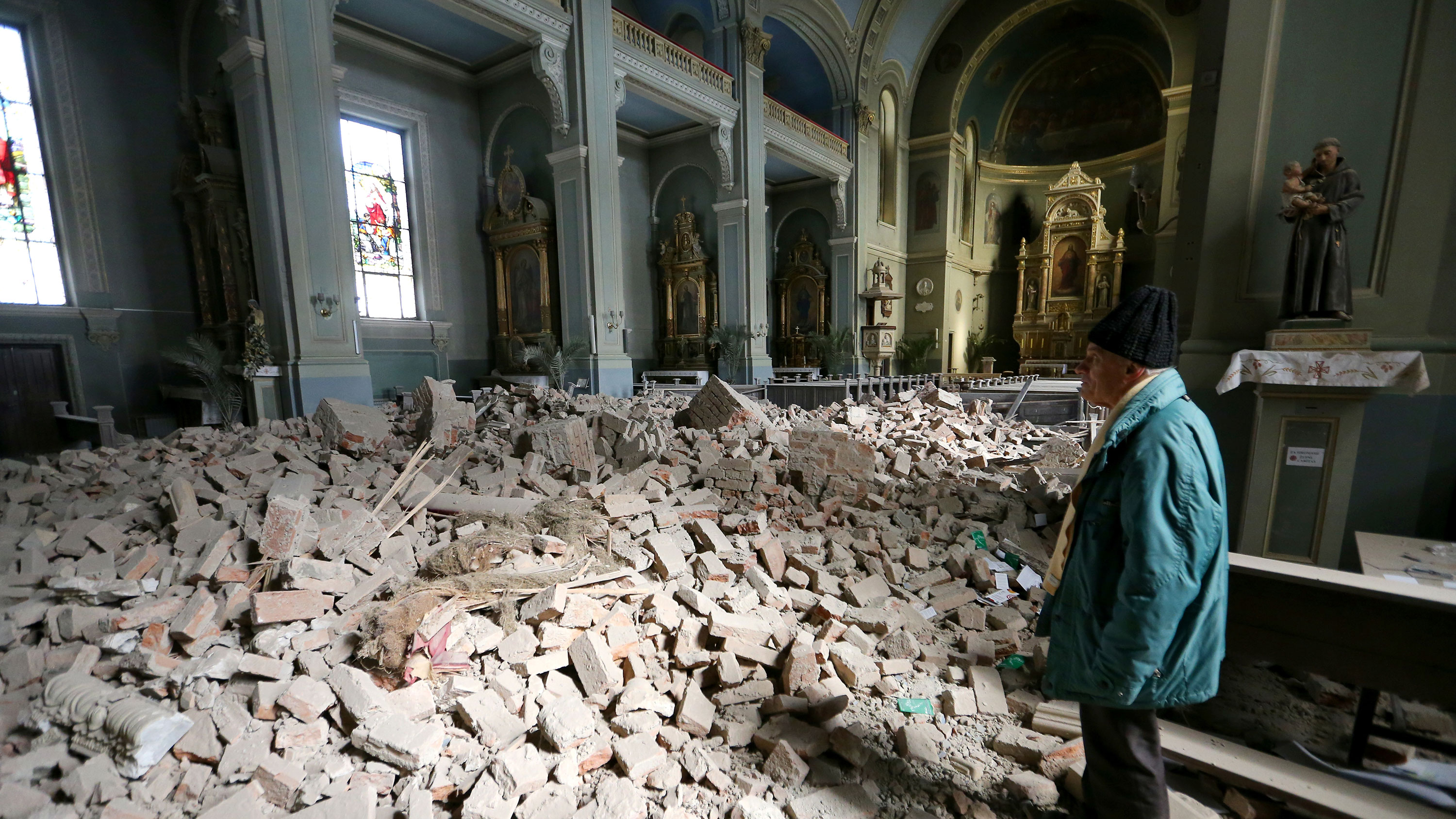 The photo shows the interior of a grand and old church that has undergone a significant amount of damage. The roof still stands but the floor of the church is filled with rubble.