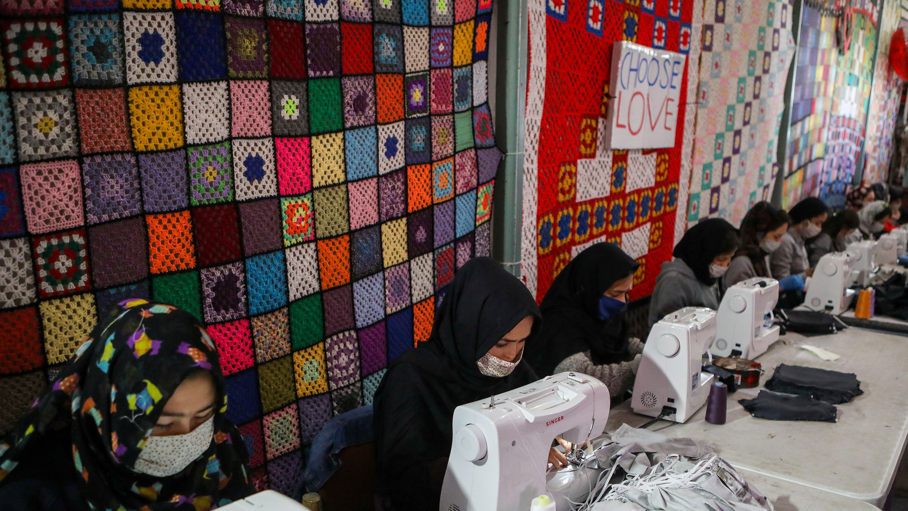 The photo shows a row of women at sewing machines sewing masks with some multicolour quilts in the background.