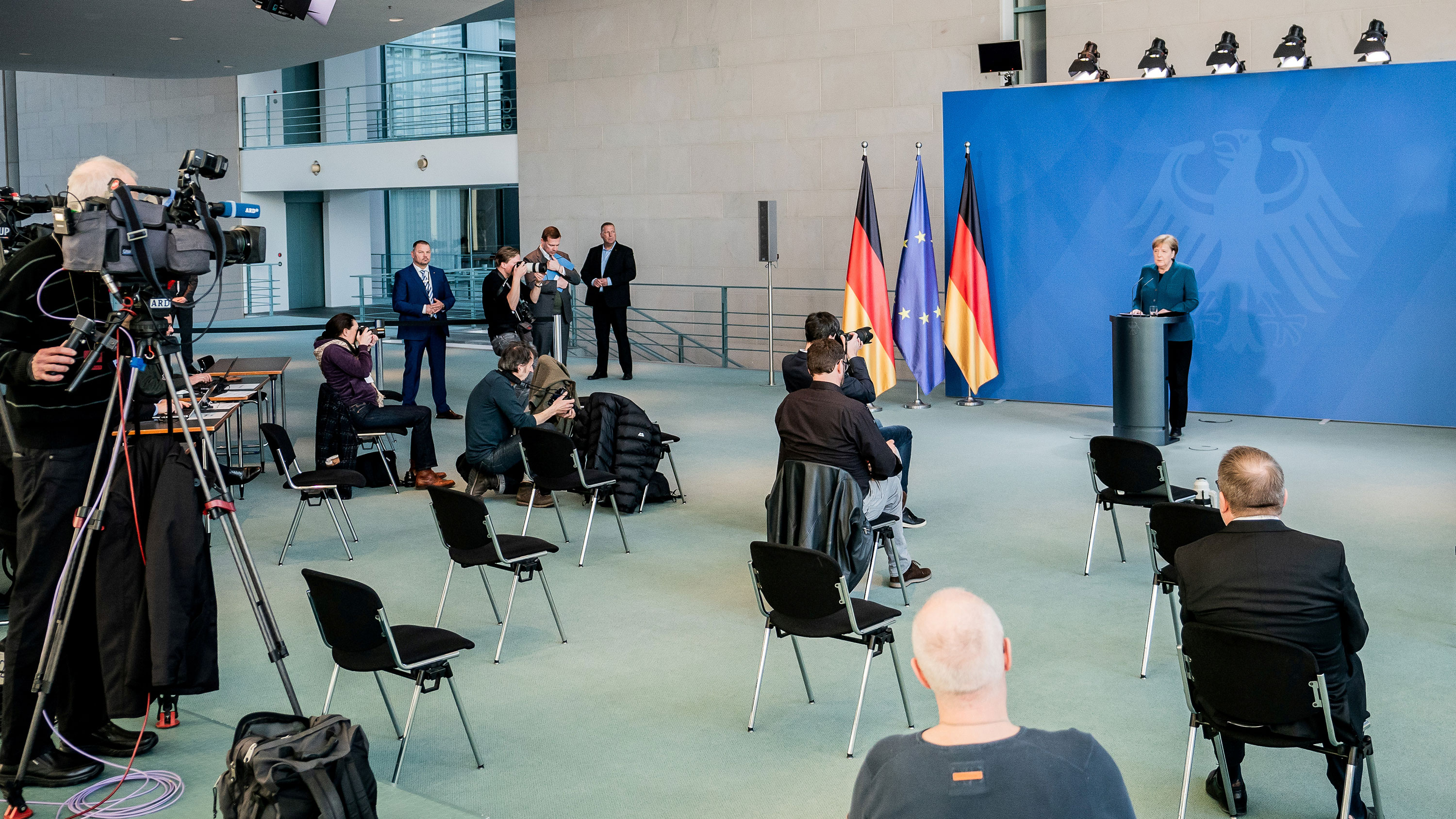 The photo shows the German Chancellor speaking to a room sparsely populated with reporters practicing social distancing.
