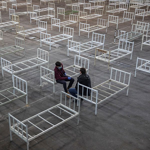 Volunteers take a break as they set up beds inside the Novi Sad Fair to accommodate people who suffer mild symptoms of coronavirus disease (COVID-19) in Novi Sad, Serbia, March 27, 2020. This is a striking image of two people resting on the edge of plain metal bed frames in a large space in which many, many more bed frames are placed. REUTERS/Marko Djurica