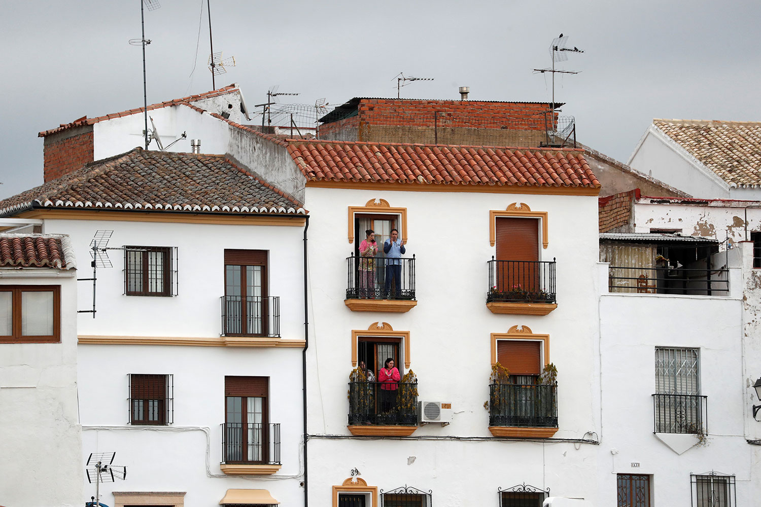The picture shows a Spanish residential building with people on the balcony cheering.