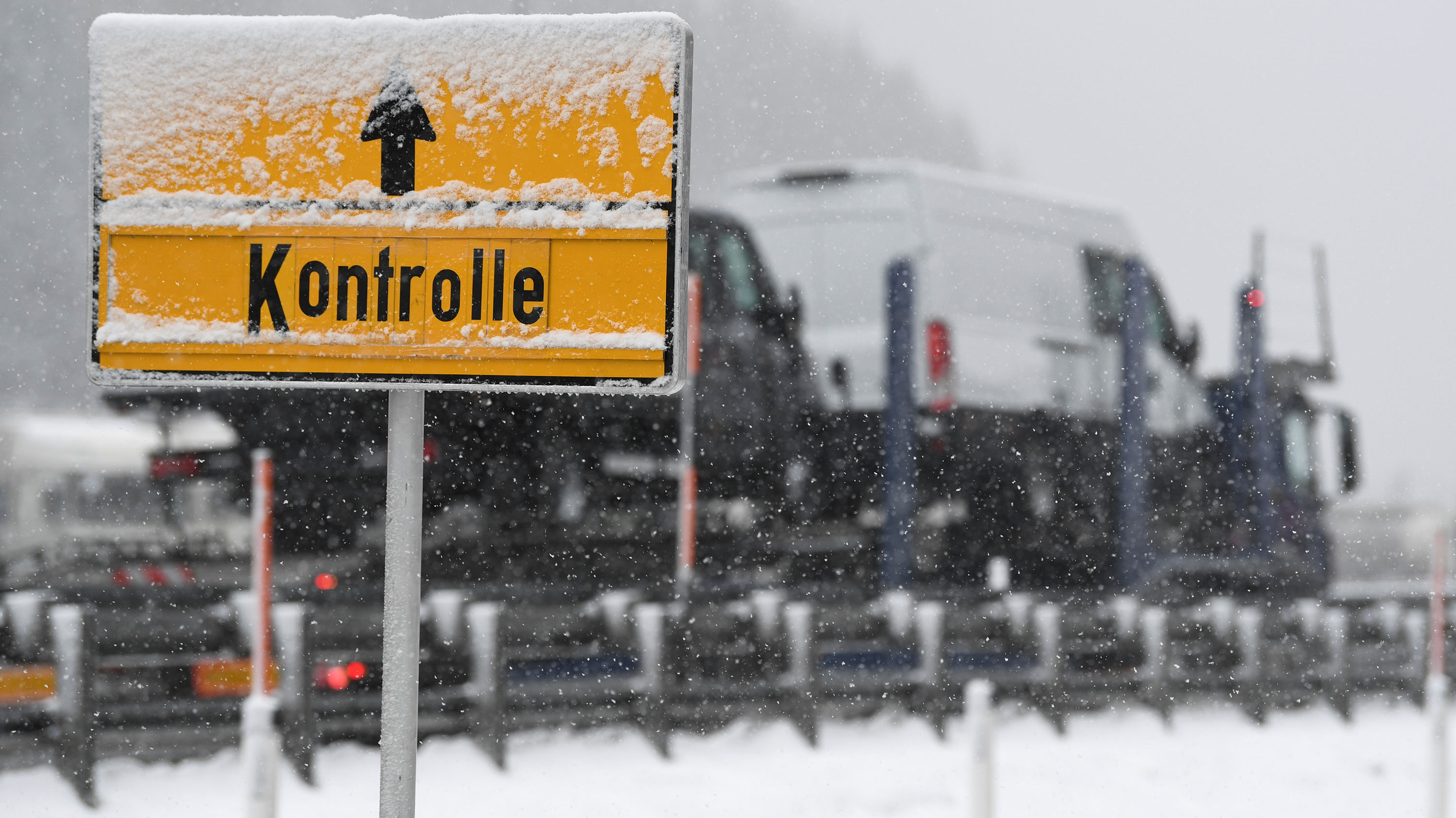 Picture shows a yellow sign and trucks waiting at the checkpoint. Snow is falling and partially obscures the sign.