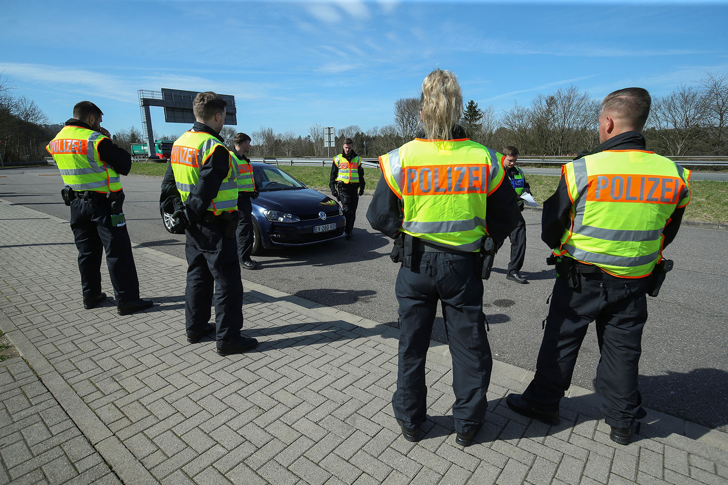 The photo shows several uniformed officers wearing yellow vests halting motorists at a checkpoint.