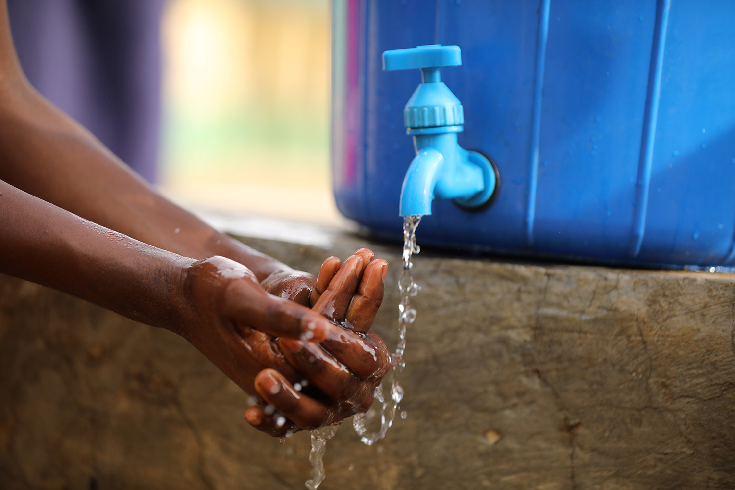 A student washes her hands after clean up at a school in response to the novel coronavirus pandemic in Abuja, Nigeria on March 20, 2020. The photo shows a pair of hands actively lathering under a water tap against a blue background. REUTERS/Afolabi Sotunde