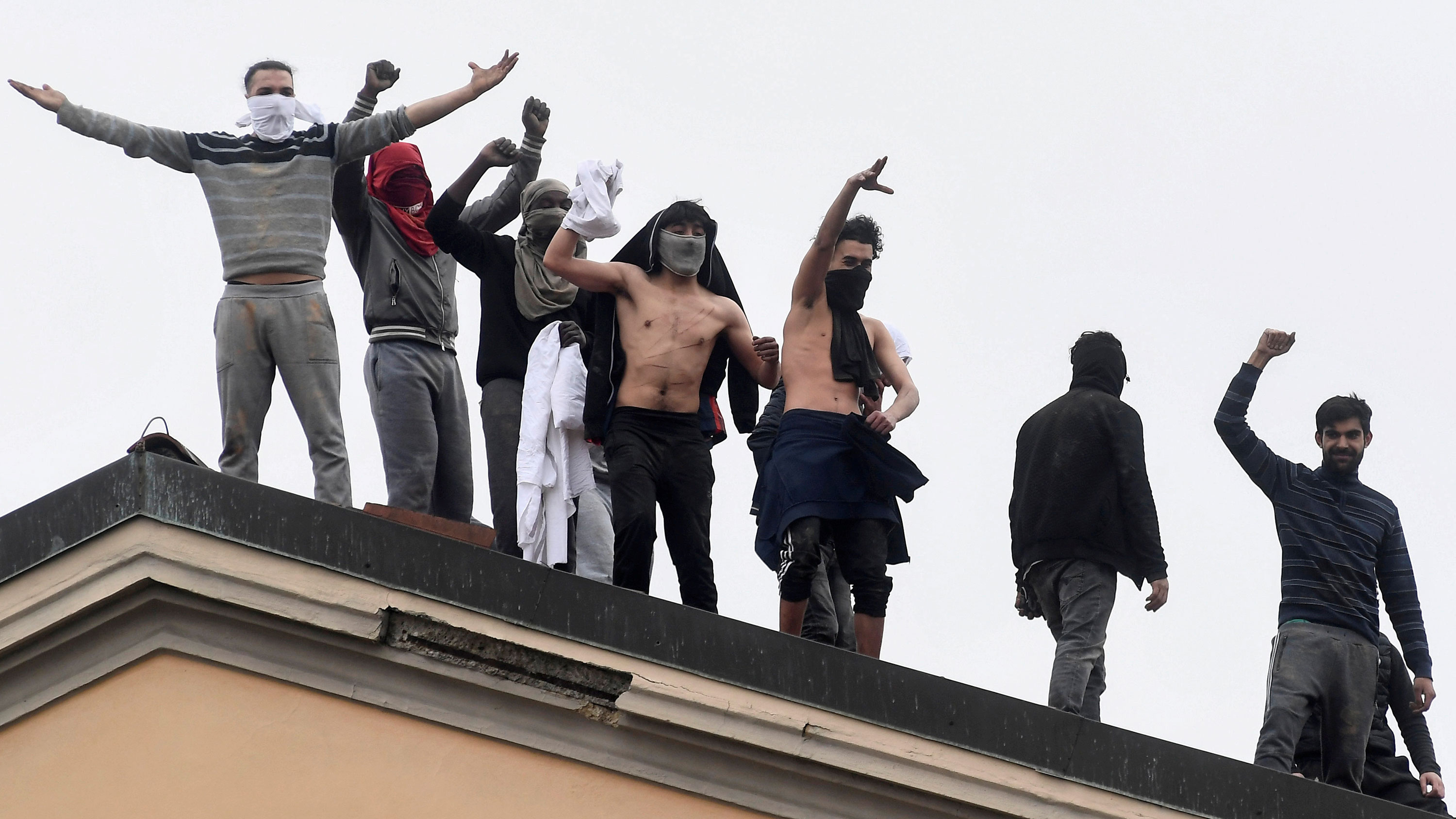 The photo shows a number of inmates, some with bandanas over their faces, on the roof of a prison building shouting at the camera, which appears to be some distance away.