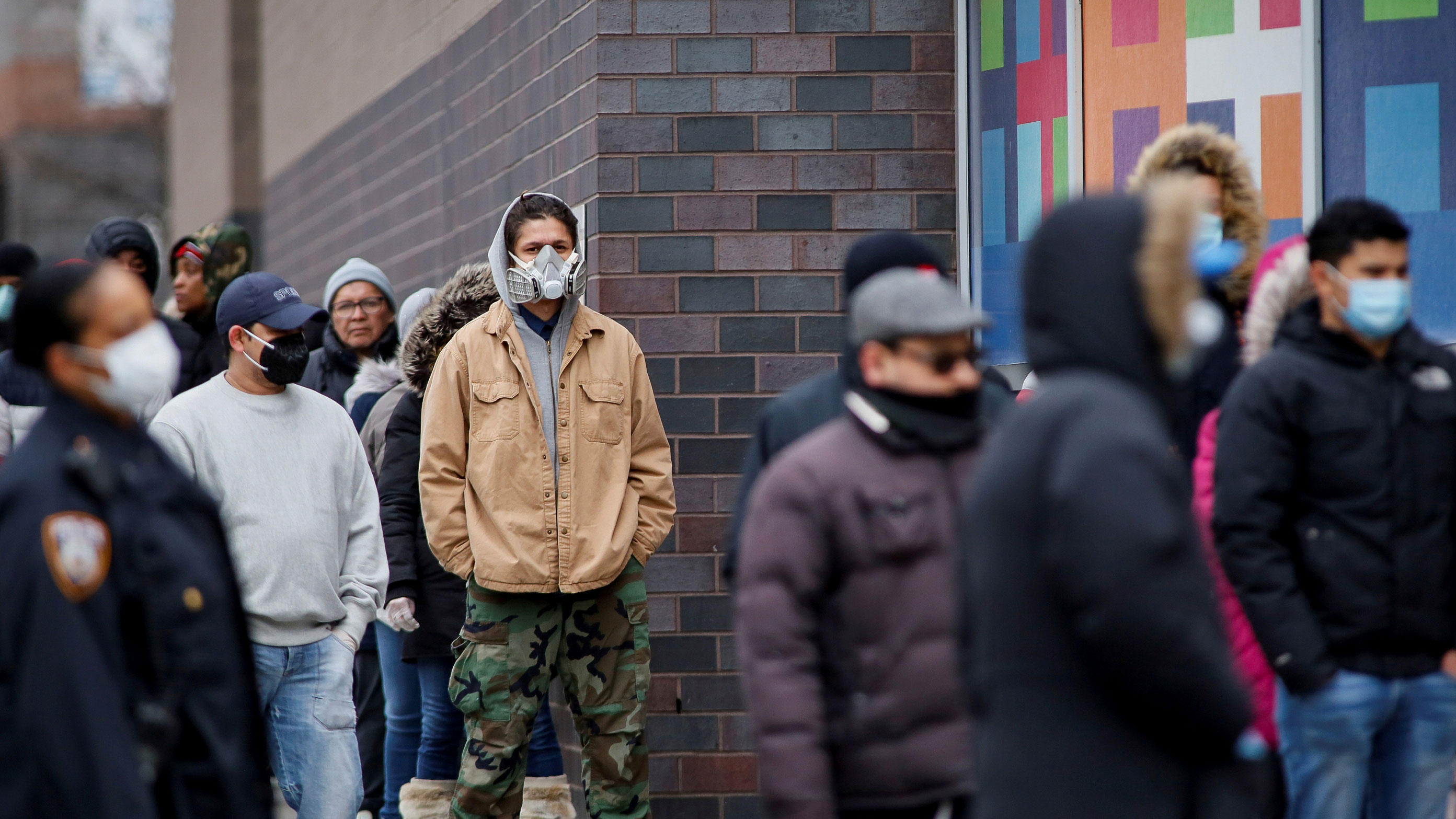 The photo shows several people in front of the hospital, several of them wearing dust masks.