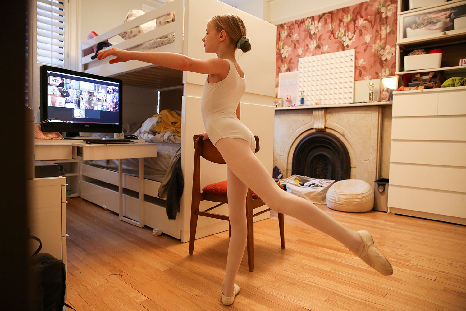 Picture shows a young pre-teen girl in a ballet uniform with one leg up in the air in front of a home computer.