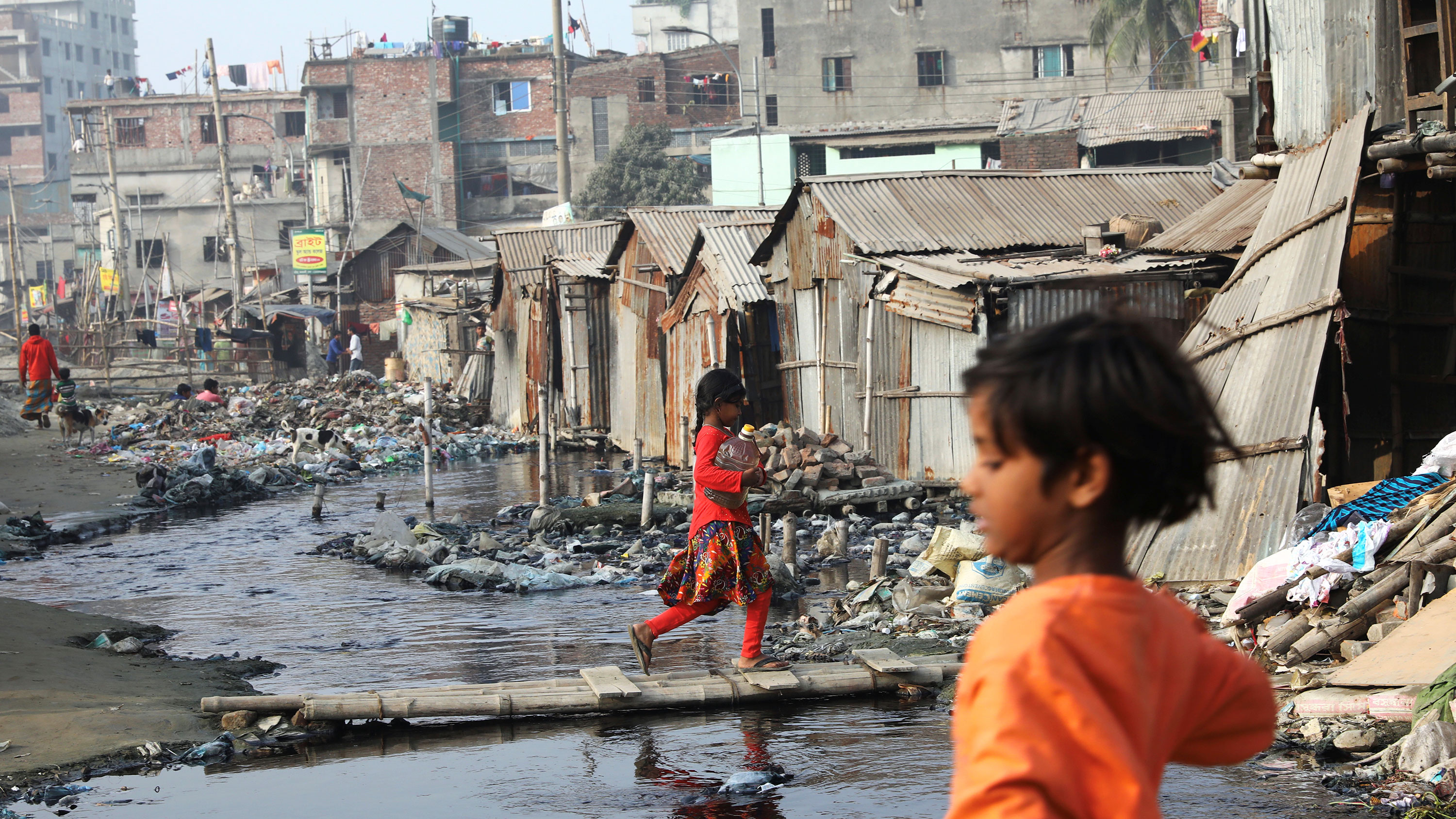 The photo shows a muddy, flooded area in front of tin shacks with a few children walking about.