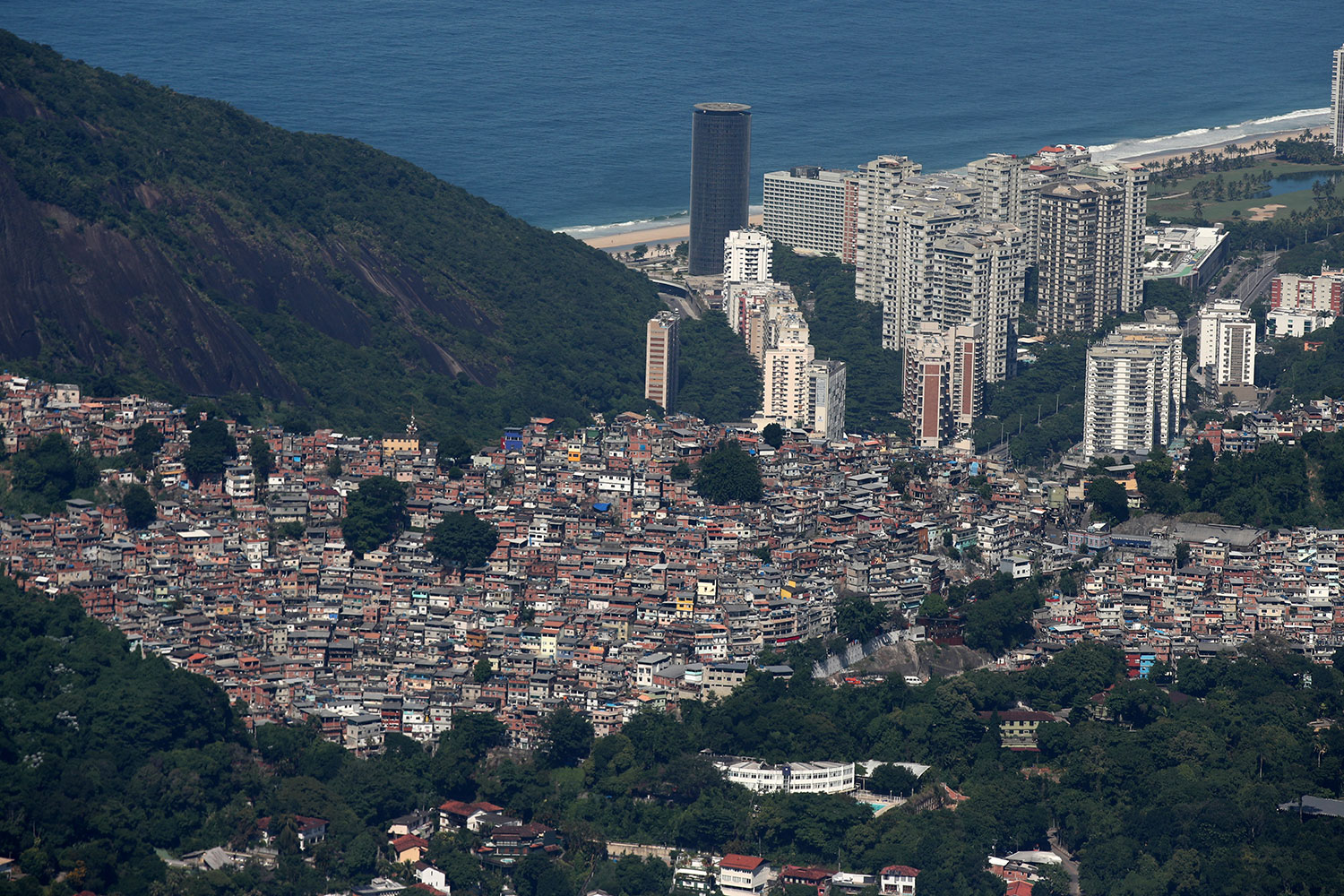 An aerial view of the Rocinha slum in Rio de Janeiro, Brazil on March 26, 2020—during the ongoing crisis over the coronavirus pandemic. The photo is a gorgeous shot taken from the sky showing the slums cascading down the mountain to the coast, which is dotted with modern skyscrapers, and the ocean beyond. REUTERS/Ricardo Moraes