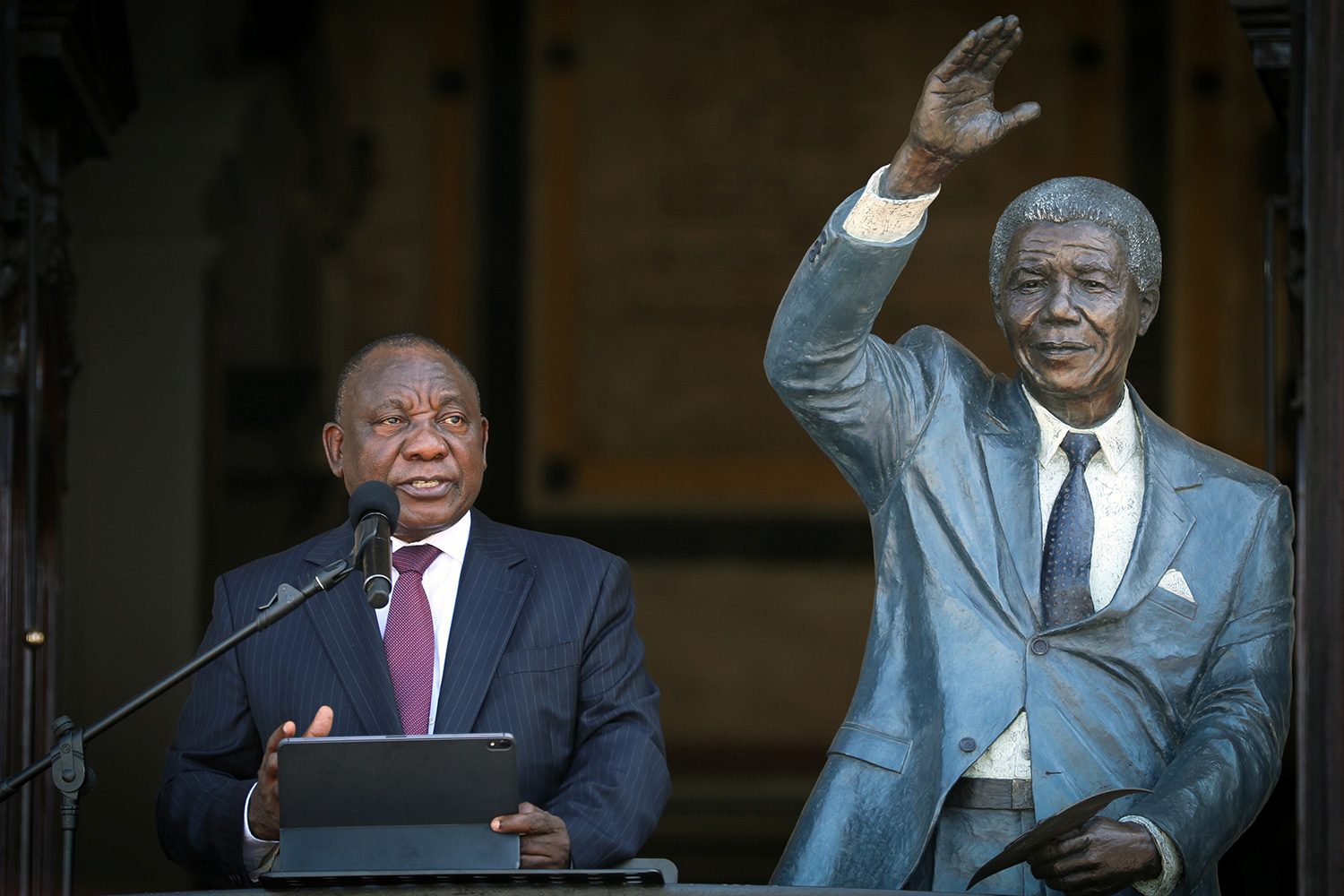 South Africa's President Cyril Ramaphosa speaks in Cape Town, South Africa on Feb 11, 2020 from the balcony where, 30 years before, Nelson Mandela gave his first speech after his release from prison. The images shows the president standing next to a life-sized statue of Nelson Mandela. REUTERS/Sumaya Hisham