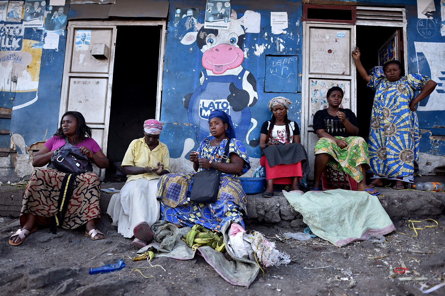 Traders sit near a deserted crossing point between Goma, Democratic Republic of Congo and Rwanda amid concerns about the spread of coronavirus on March 23, 2020. The photo shows a number of women sitting in front of a storefront painted blue and adorned by a large cartoon figure of a cow giving a thumb's up. REUTERS/Olivia Acland