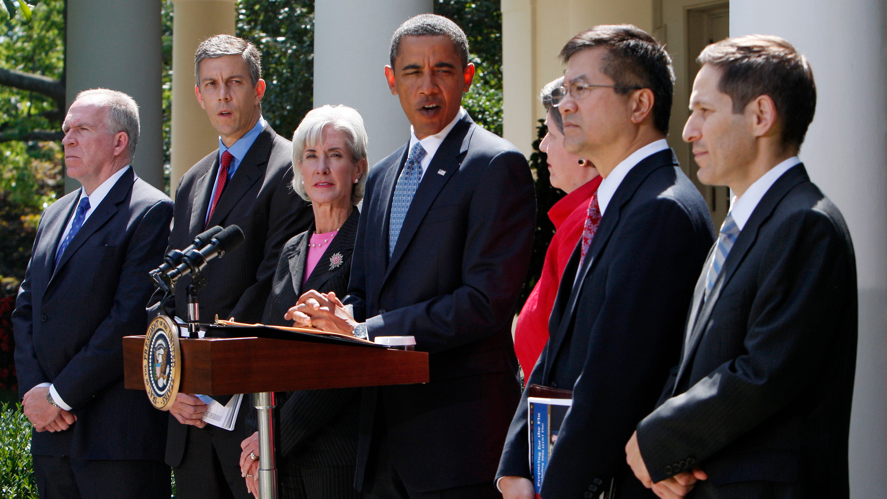 Obama is standing in front of microphones looking toward the camera surrounded by cabinet officials.