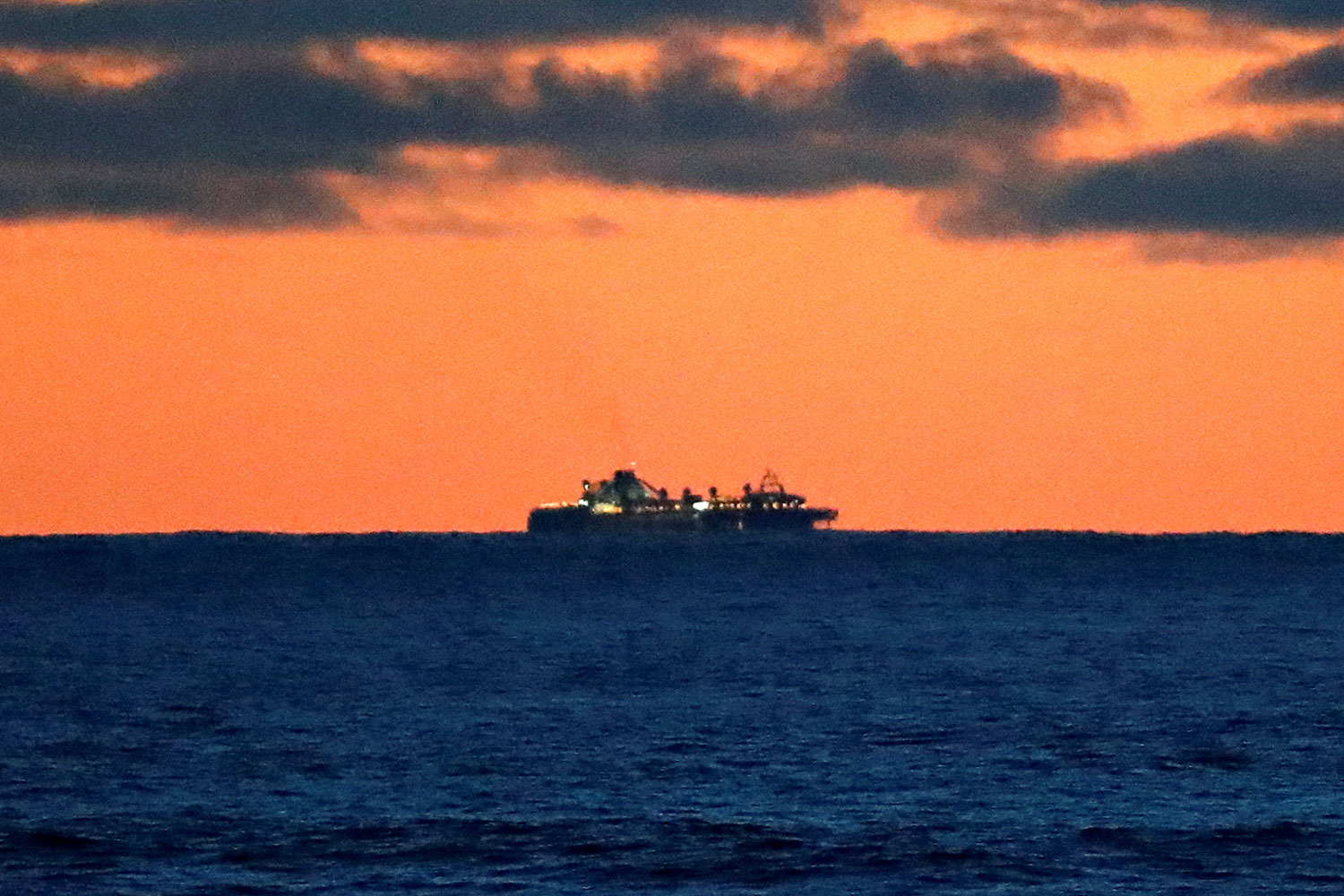 The photo is an open ocean shot of the large cruise ship far off in the distance against a brilliant sunset.