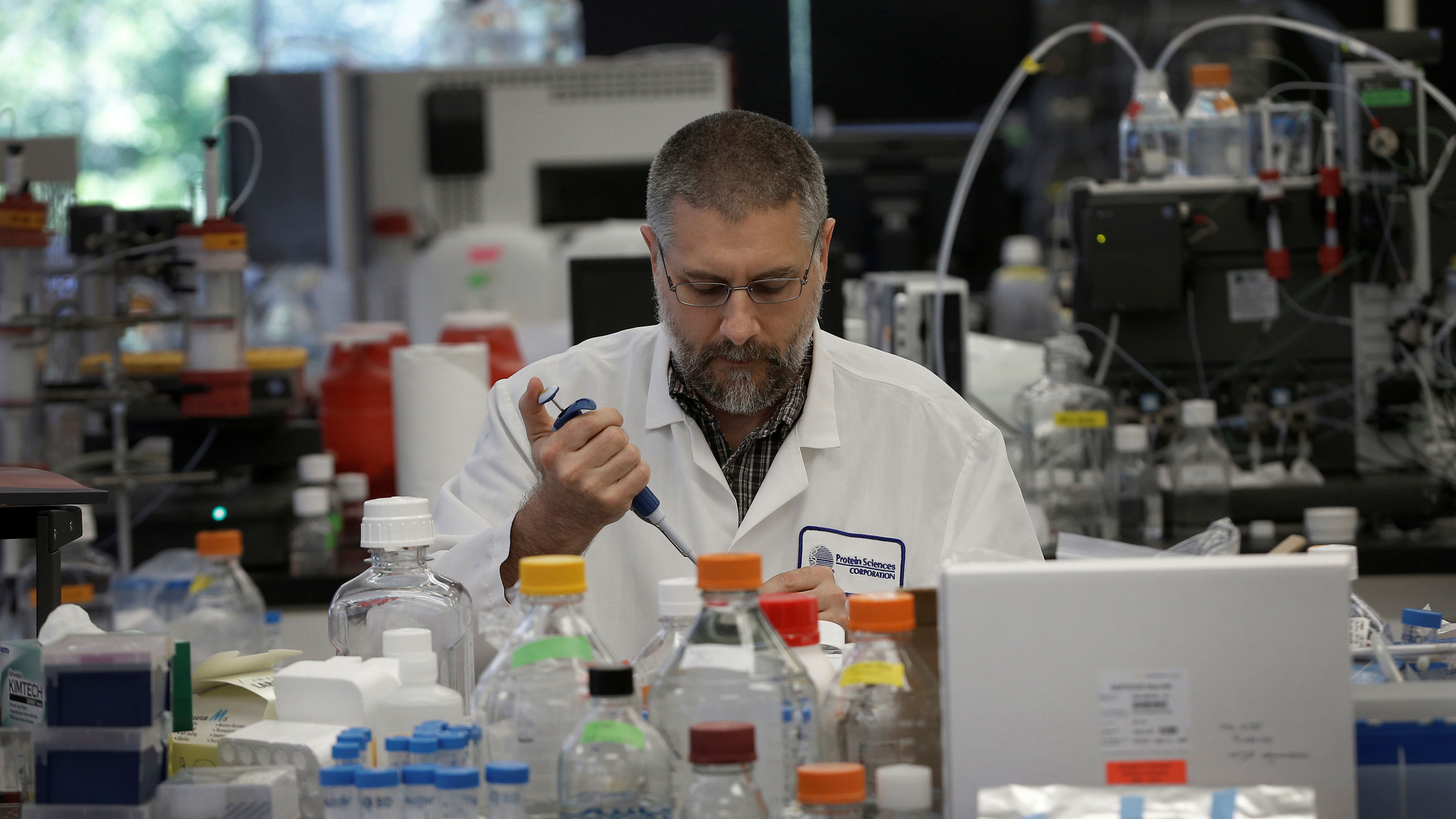 Picture shows the researcher pipetting into vials in a laboratory surrounded by chemical bottles and instruments.