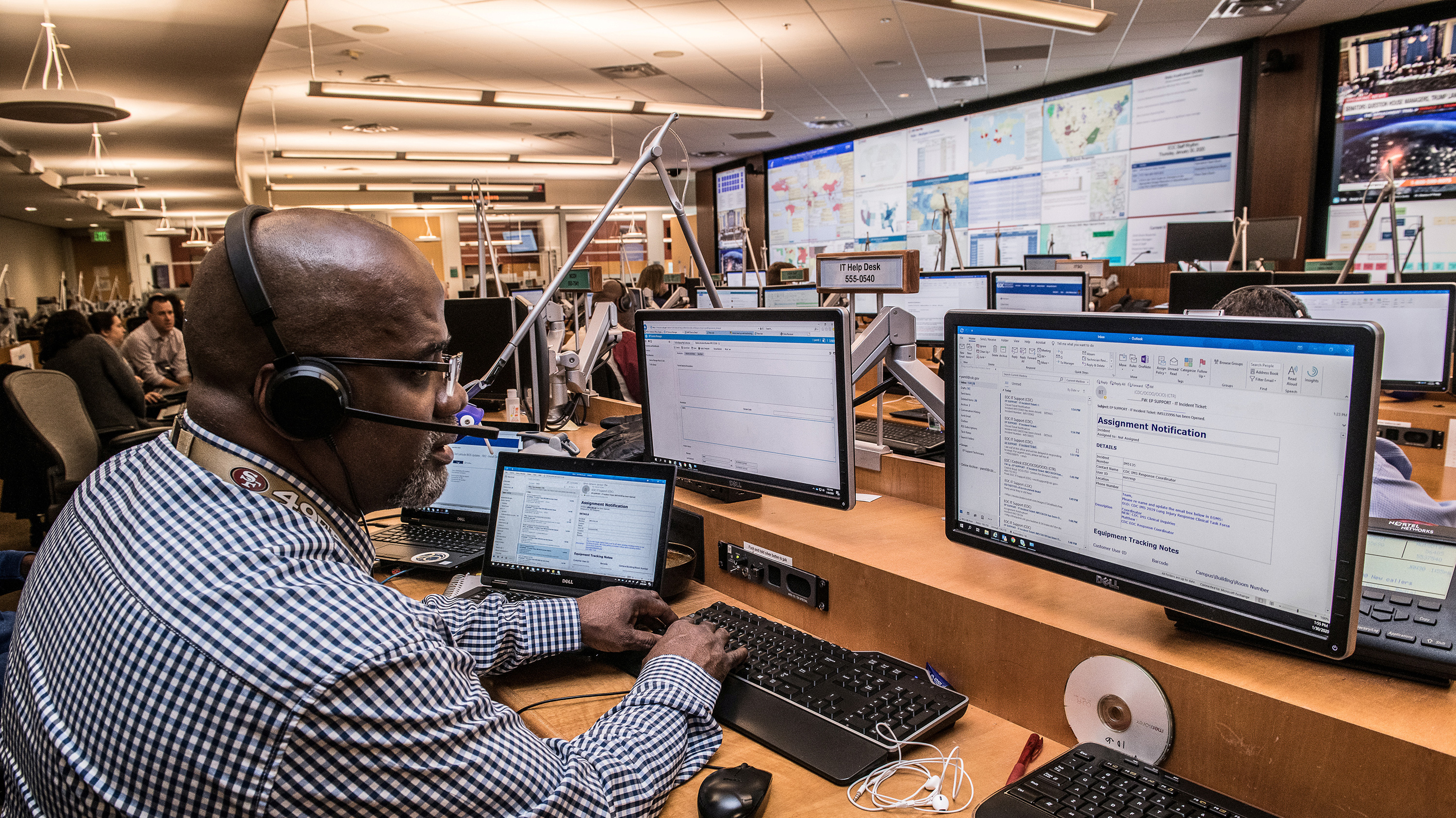 Picture shows a man in a large operations room with numerous huge display screens showing data.