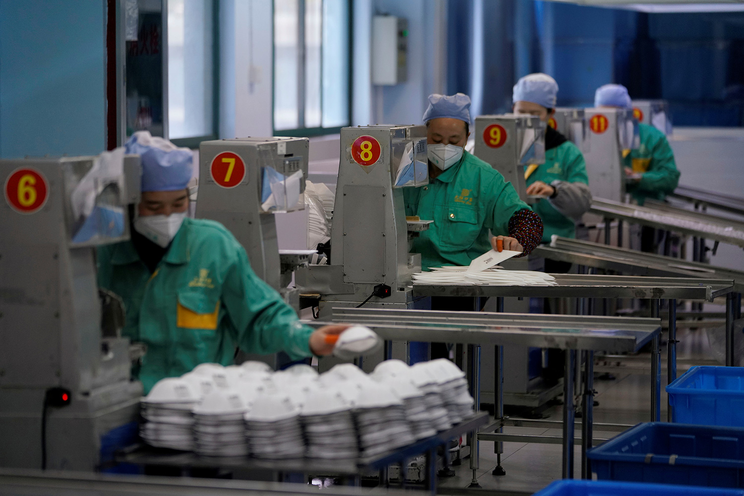 The photo shows a row of workers piling up masks as they roll off machinery. Each one is at a workstation numbered six through twelve.