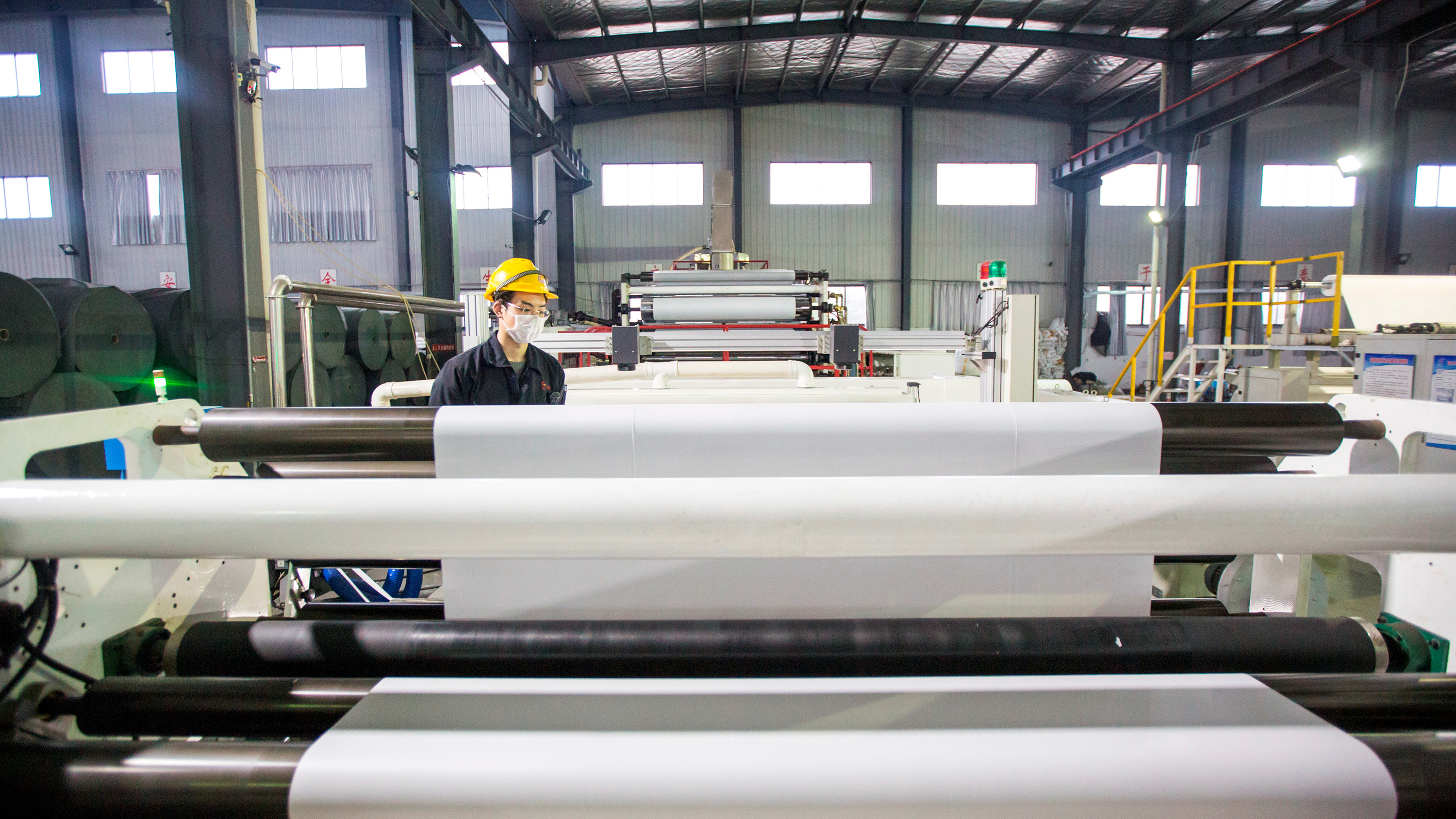 Picture shows a single worker standing amid machinery that has massive rolls of material on spools.